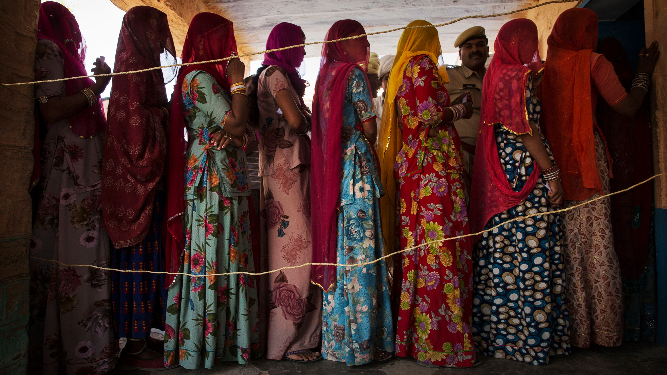 Indian women wait to vote at a polling station in the Jodhpur District in the desert state of Rajasthan, India, on April 17, 2014. (Credit: Kevin Frayer / Getty Images)