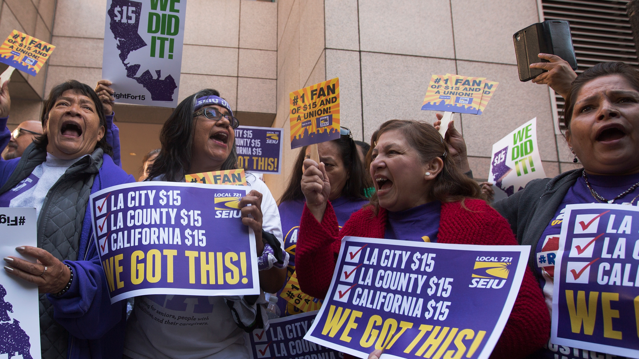 Service Employees International Union members celebrate after Jerry Brown signed landmark legislation SB 3 into law on April 4, 2016 in Los Angeles. (Credit: David McNew/Getty Images)