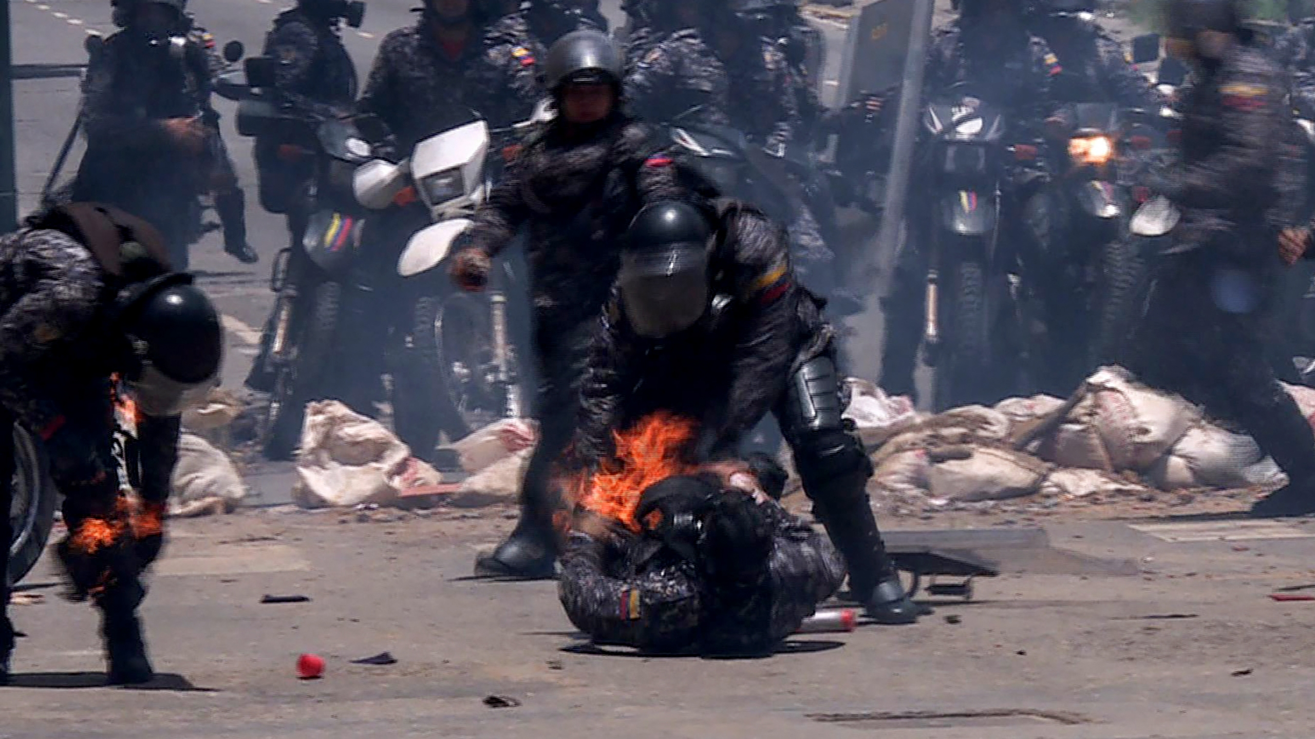 Video grab showing police officers helping a colleague who caught fire after an explosive device went off as they rode past during a protest against the elections for a Constituent Assembly in Caracas on July 30, 2017. (Credit: Leo Ramirez/AFP/Getty Images)
