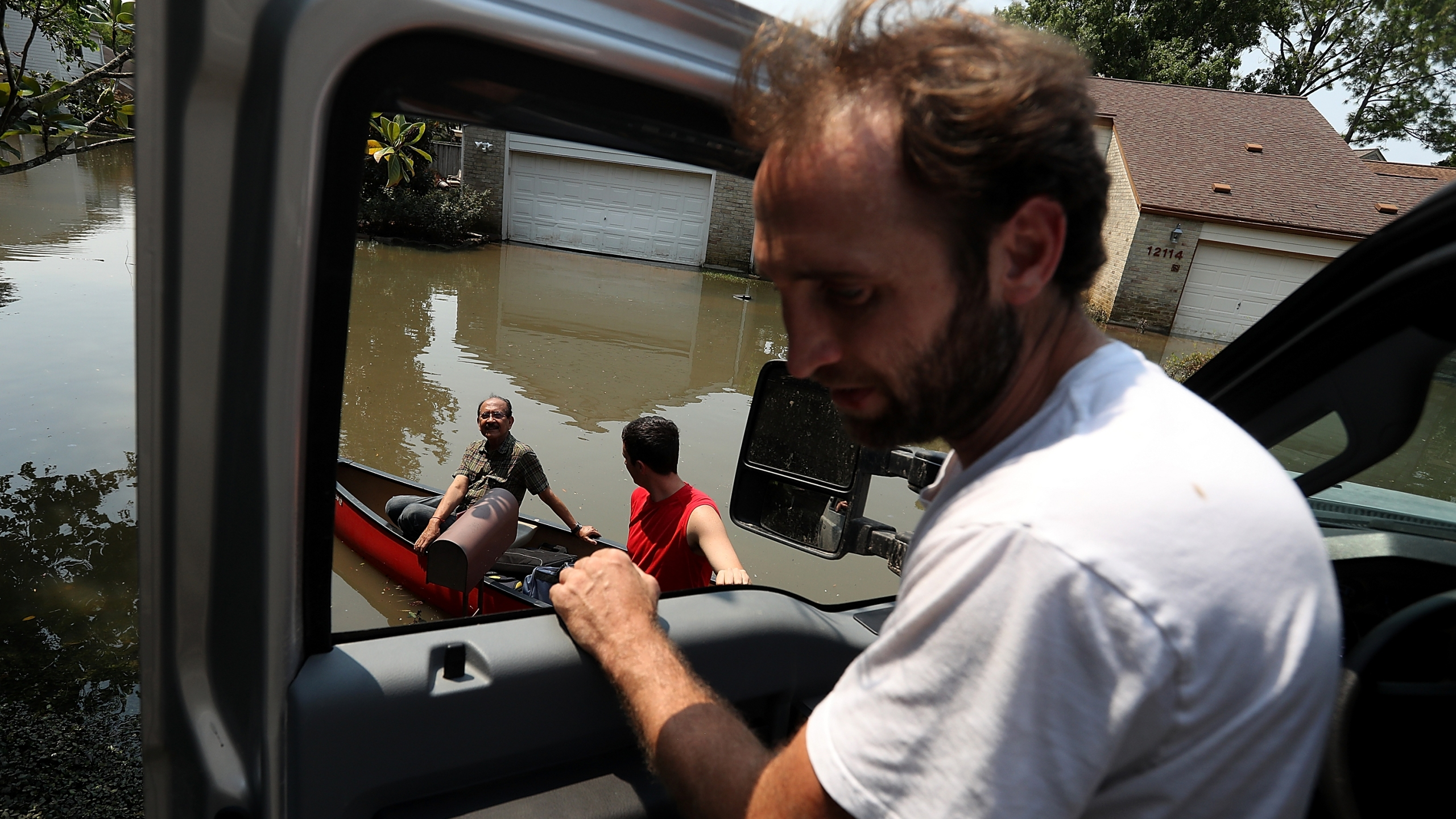 Chris Ginter (right) talks to residents on a boat in a flooded neighborhood on Sept. 6, 2017 in Houston. (Credit: Justin Sullivan/Getty Images)