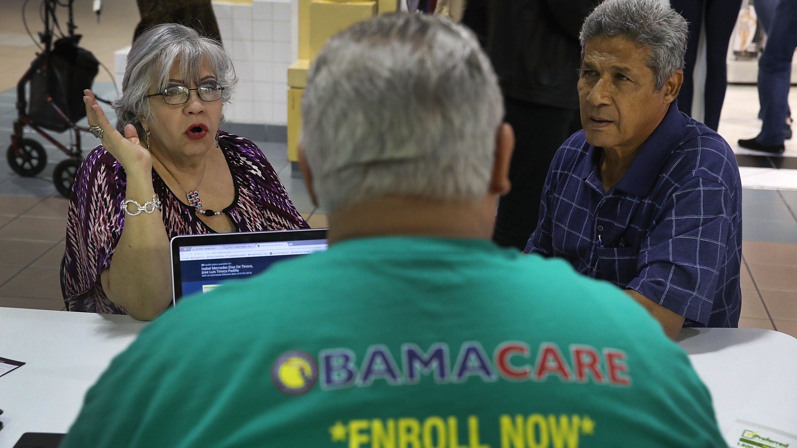 Isabel Diaz Tinoco, left, and Jose Luis Tinoco speak with Otto Hernandez, an insurance agent from Sunshine Life and Health Advisors, as they shop for insurance under the Affordable Care Act at a store setup in the Mall of Americas on Nov. 1, 2017, in Miami, Florida. (Credit: Joe Raedle/Getty Images)
