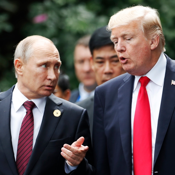 US President Donald Trump (R) and Russia's President Vladimir Putin talk in the central Vietnamese city of Danang on November 11, 2017. (Credit: JORGE SILVA/AFP/Getty Images)