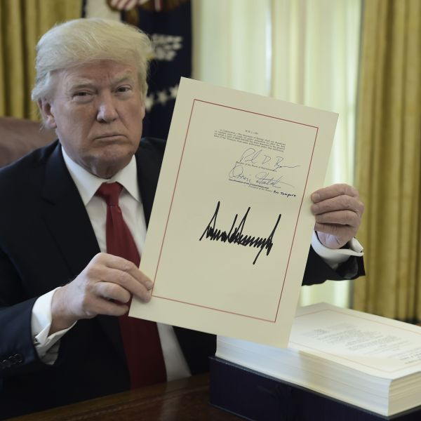 President Trump holds up a copy of the tax reform bill he signed in the Oval Office on Dec. 22, 2017. (Credit: Brendan Smialowski / AFP / Getty Images)
