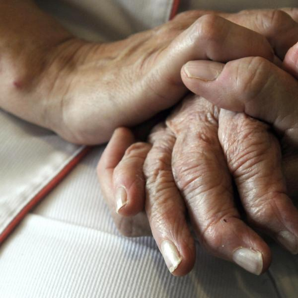 A nurse holds the hands of a person suffering from Alzheimer's disease in eastern France in this September 2009 file photo. (Credit: Sebastien Bozon / AFP / Getty Images)