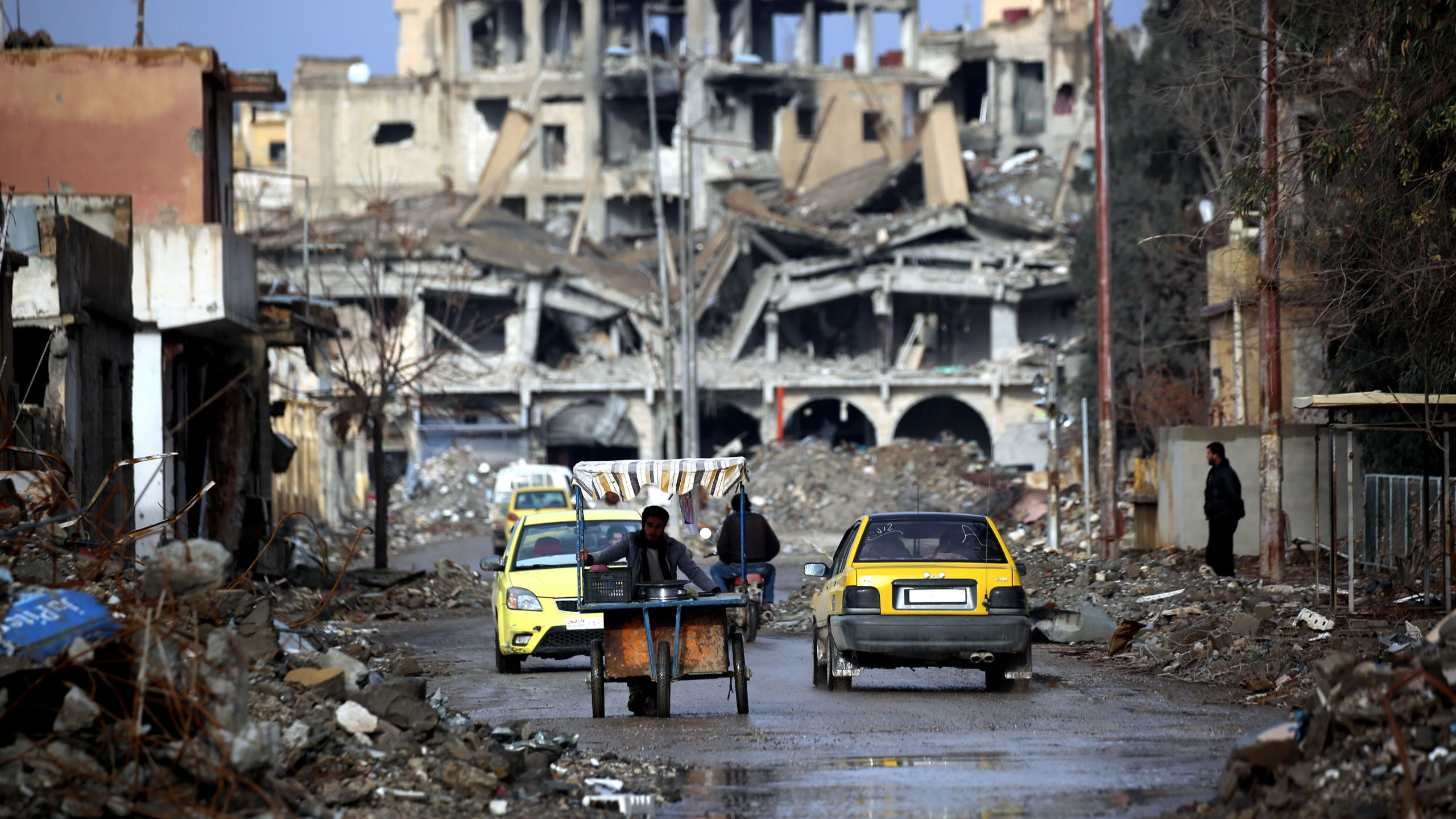 Syrians are shown traveling along a destroyed street in Raqqa on February 18, 2018. (Credit: Delil Souleiman/AFP/Getty Images)