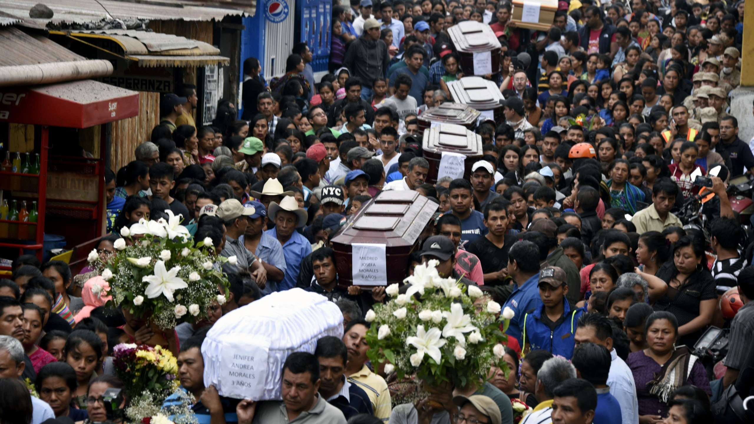 Residents carry the coffins of seven people who died following the eruption of the Fuego volcano, along the streets of Alotenango municipality, Sacatepequez, about 65 km southwest of Guatemala City, on June 4, 2018. (Credit: JOHAN ORDONEZ/AFP/Getty Images)