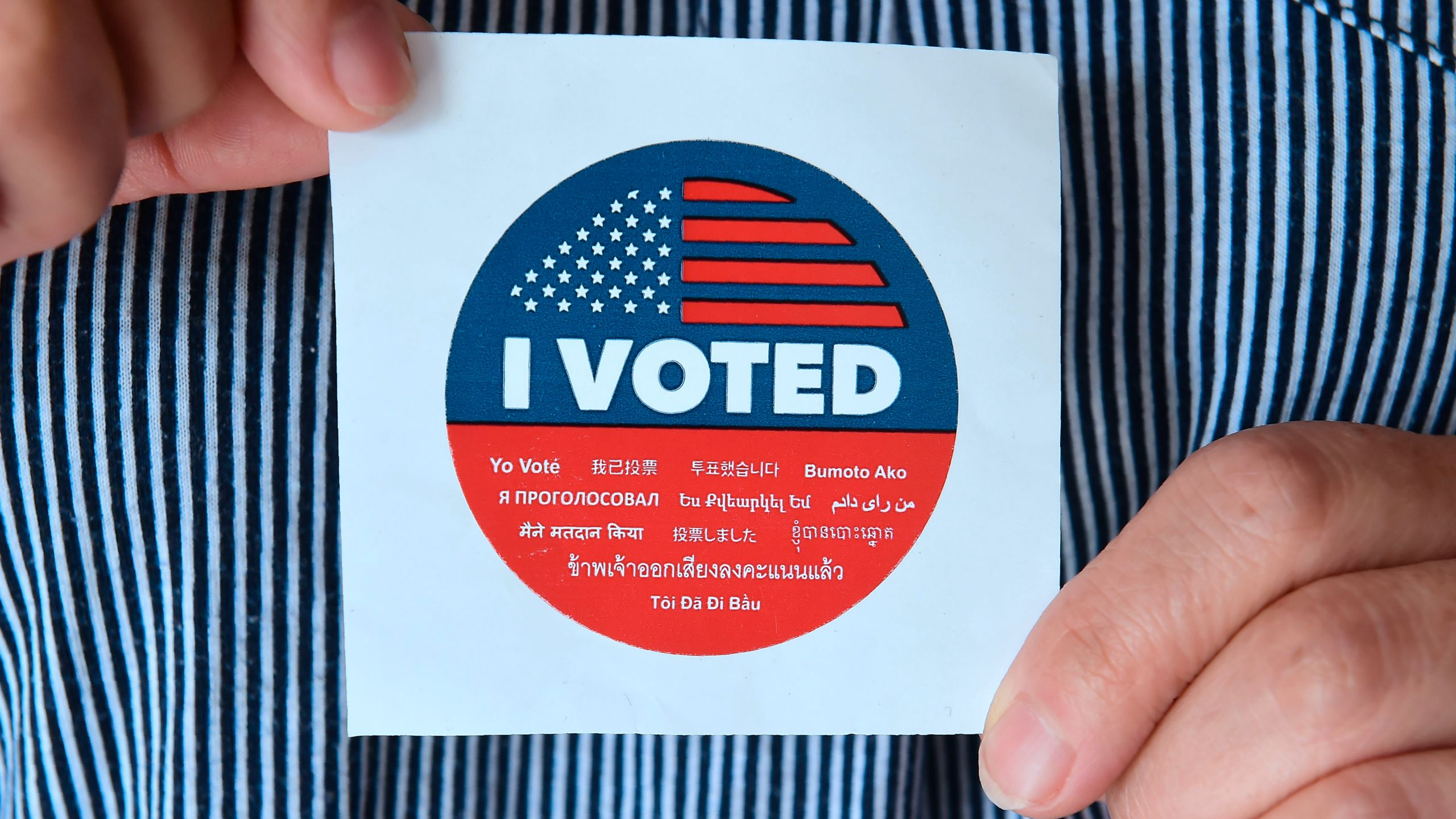 A woman displays a sticker given to voters outside a polling station in Los Angeles on June 5, 2018. (Credit: Frederic J. Brown / AFP / Getty Images)