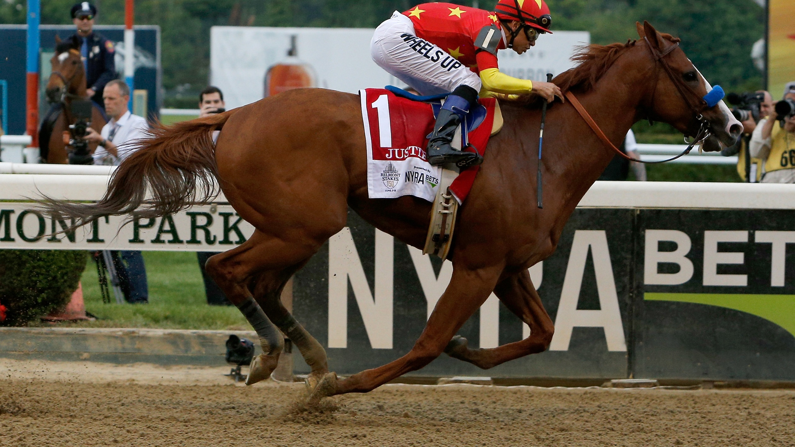 Justify #1, ridden by jockey Mike Smith, crosses the finish line to win the 150th running of the Belmont Stakes at Belmont Park on June 9, 2018, in Elmont, New York. (Michael Reaves/Getty Images)