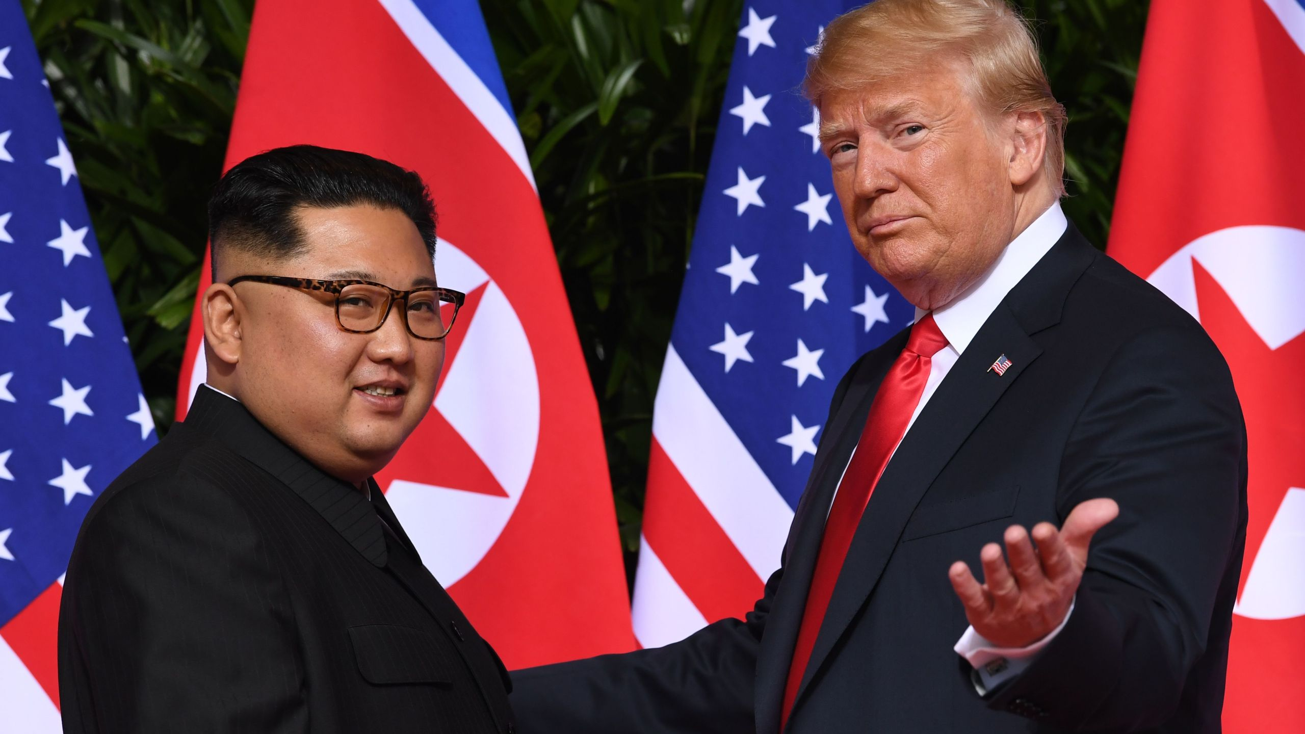 President Donald Trump gestures as he meets with North Korea's leader Kim Jong Un at the start of their historic summit in Singapore on June 12, 2018. (Credit: Saul Loeb / AFP / Getty Images)