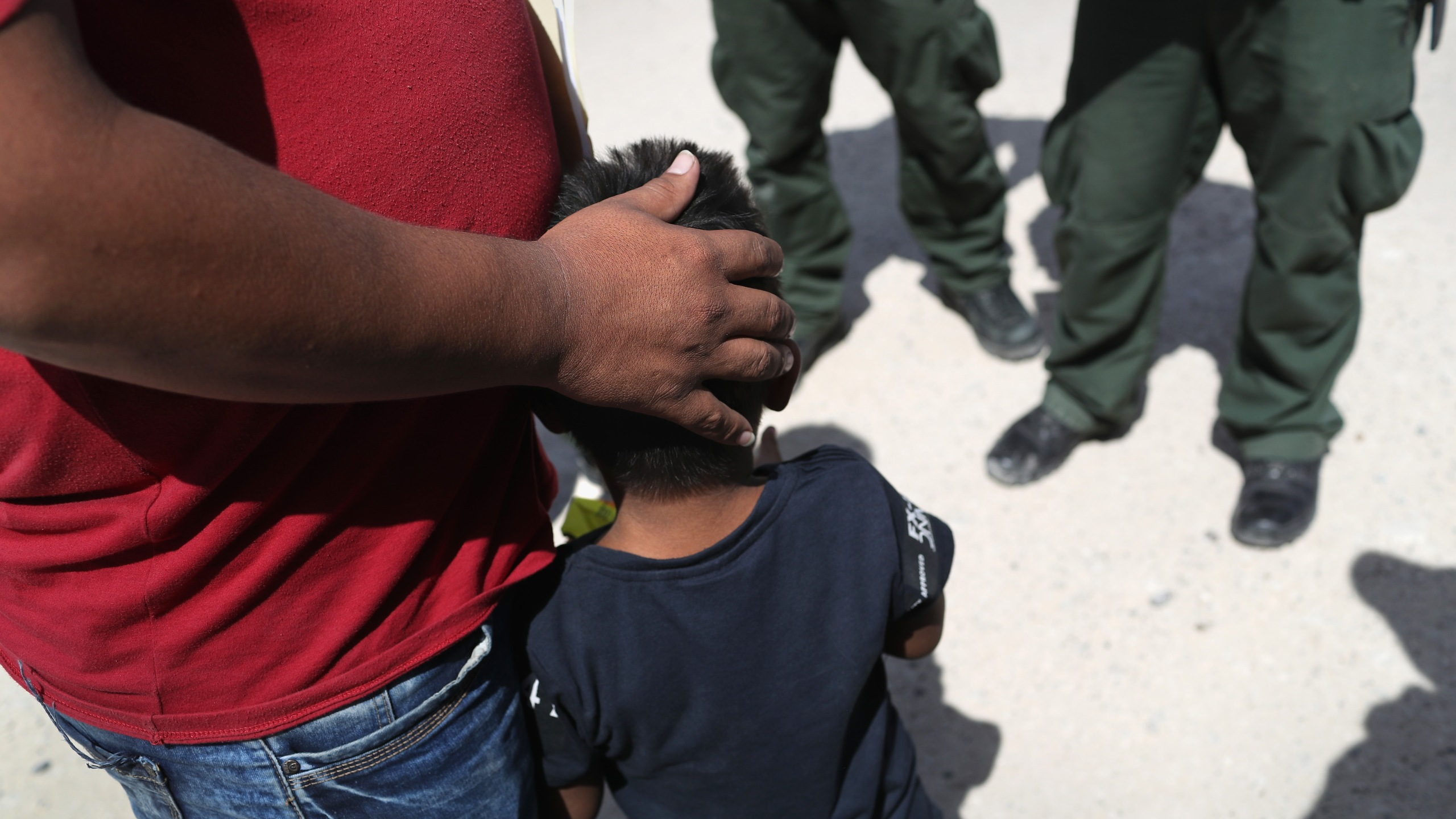 Border Patrol agents take a father and son from Honduras into custody near the U.S.-Mexico border on June 12, 2018, near Mission, Texas. (Credit: John Moore / Getty Images)