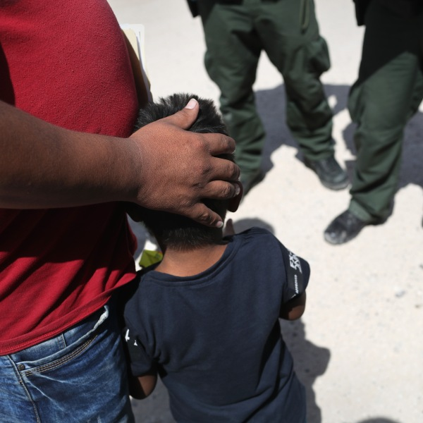U.S. Border Patrol agents take a father and son from Honduras into custody near the U.S.-Mexico border on June 12, 2018 near Mission, Texas. (Credit: John Moore/Getty Images)
