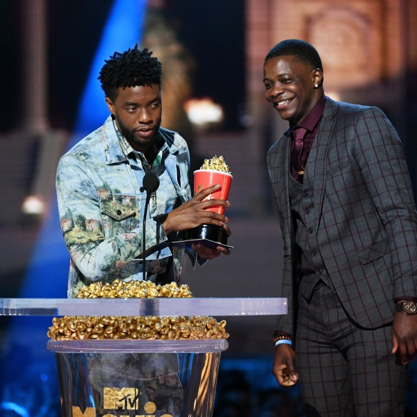 """Actor Chadwick Boseman, winner of the Best Hero award for his role in """"Black Panther,"""" presents his trophy to James Shaw Jr. onstage during the 2018 MTV Movie And TV Awards at Barker Hangar on June 16, 2018, in Santa Monica. (Credit: Kevin Winter/Getty Images for MTV)"""
