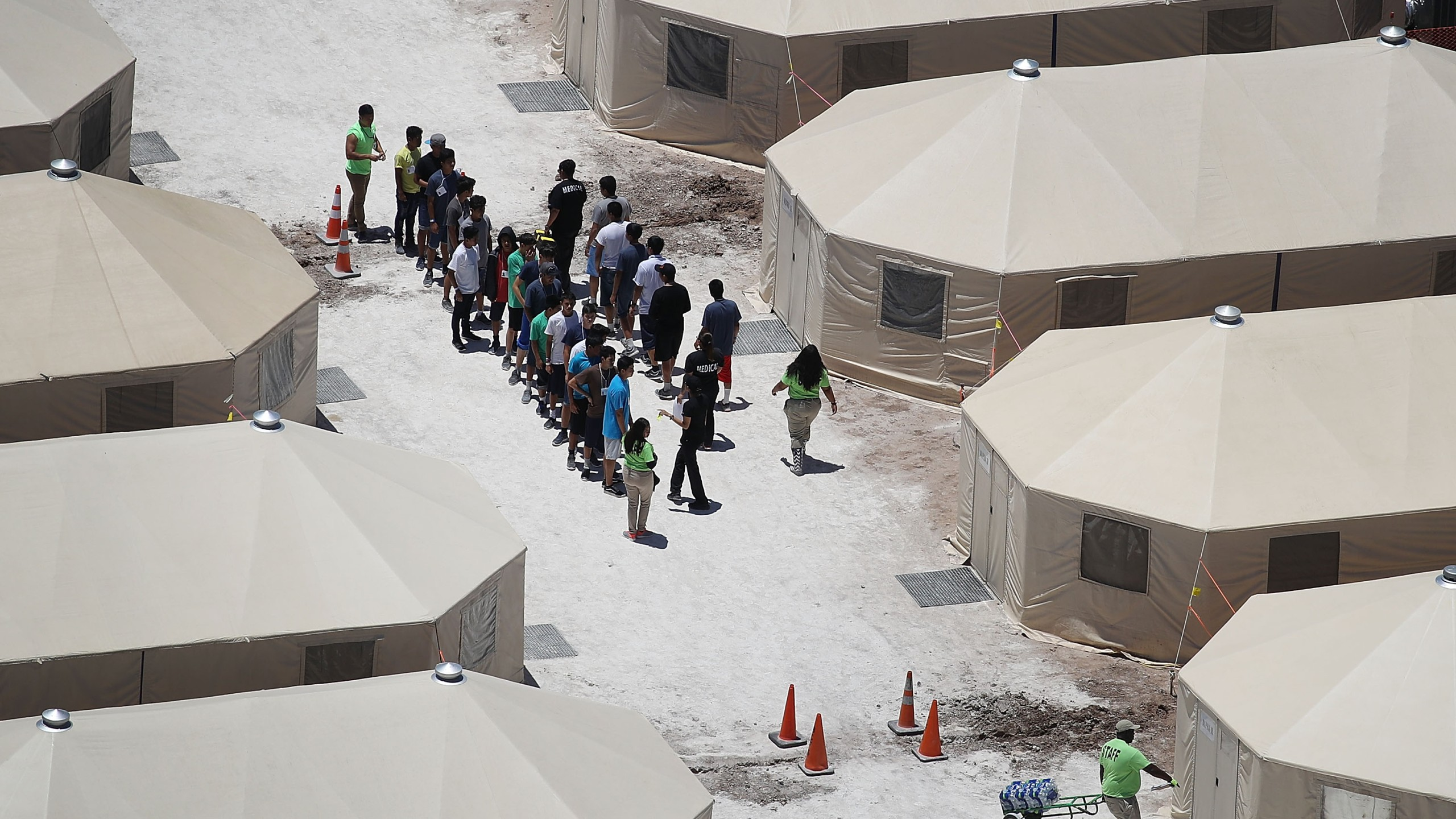 Children and workers are seen at a tent encampment recently built near the Tornillo Port of Entry on June 19, 2018 in Tornillo, Texas. The Trump administration is using the Tornillo tent facility to house immigrant children separated from their parents after they were caught entering the U.S. under the administration's zero tolerance policy. (Credit: Joe Raedle/Getty Images)