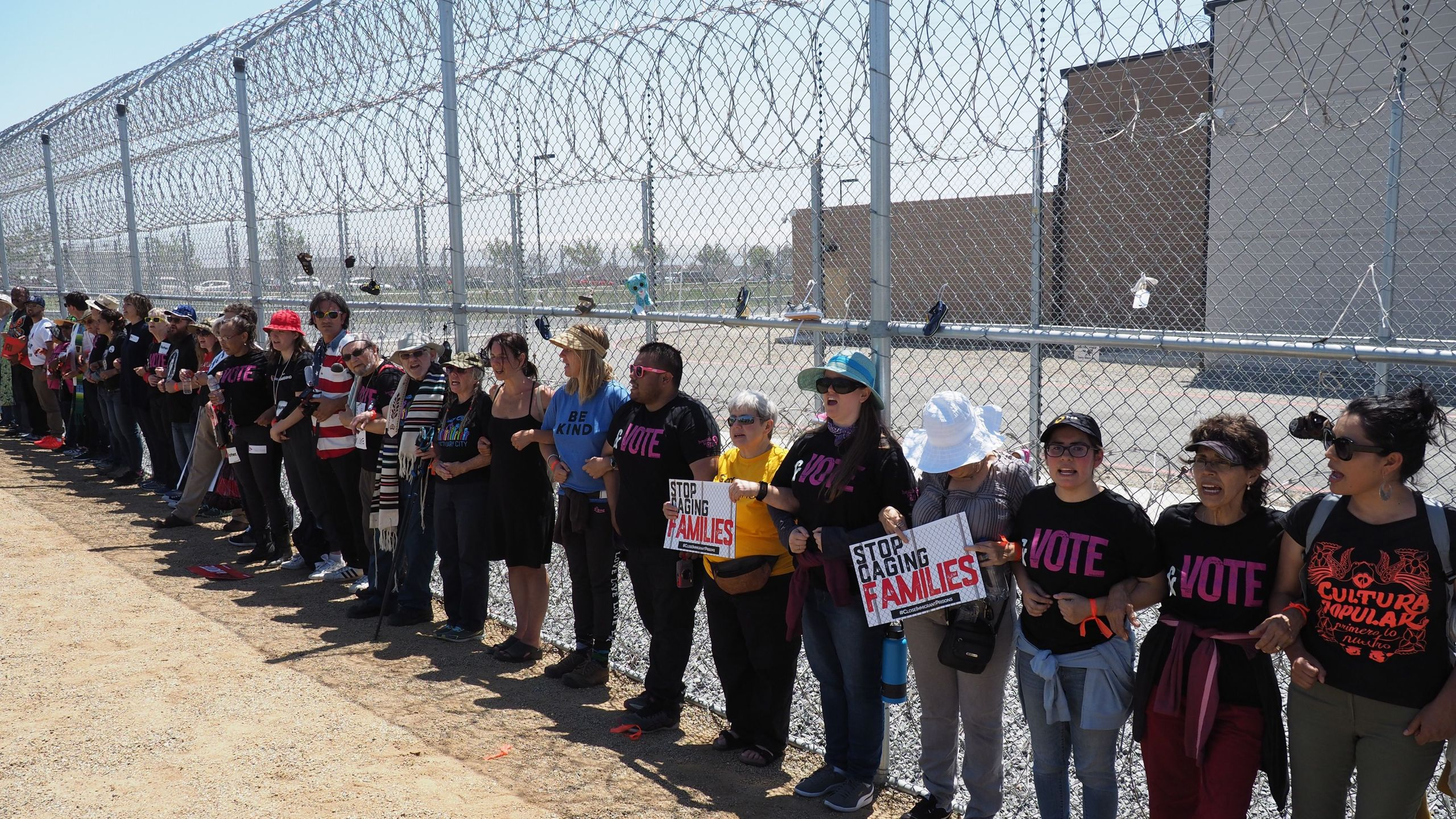 Protestors link arms after tying children's shoes and keys on the fence outside the Otay Mesa Detention Center during a demonstration against a Trump administration policy that separated migrant children from parents, in San Diego on June 23, 2018. (Credit: Robyn Beck / AFP / Getty Images)