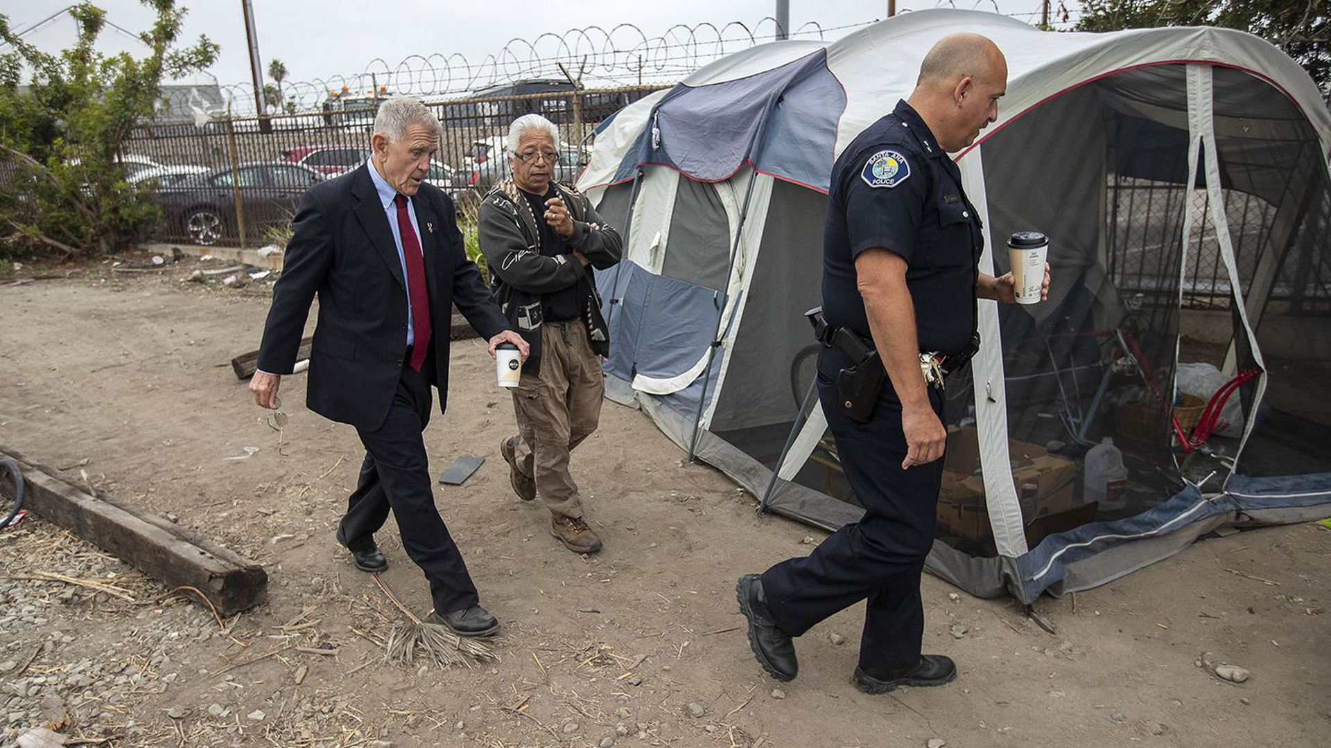 U.S. District Judge David Carter, left, homeless activist Lou Noble and Deputy Chief Ken Gominsky of the Santa Ana Police Department walk past a tent along railroad tracks near Main Street in Santa Ana on June 5, 2018. (Credit: Scott Smeltzer / Daily Pilot)