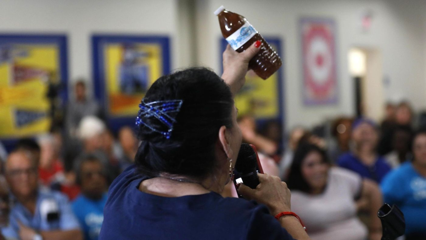 During a town hall June 18, 2018, Compton resident Maria Villarreal holds up a bottle containing brown water that she said came from the tap in her home. (Credit: Genaro Molina / Los Angeles Times)