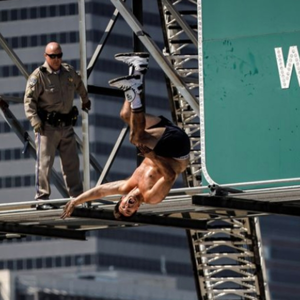 California Highway Patrol officers watch as a man who had scaled a freeway sign and shut down the southbound 110 Freeway does a backflip onto massive inflatable cushions set up below in downtown Los Angeles. (Credit: Marcus Yam / Los Angeles Times)