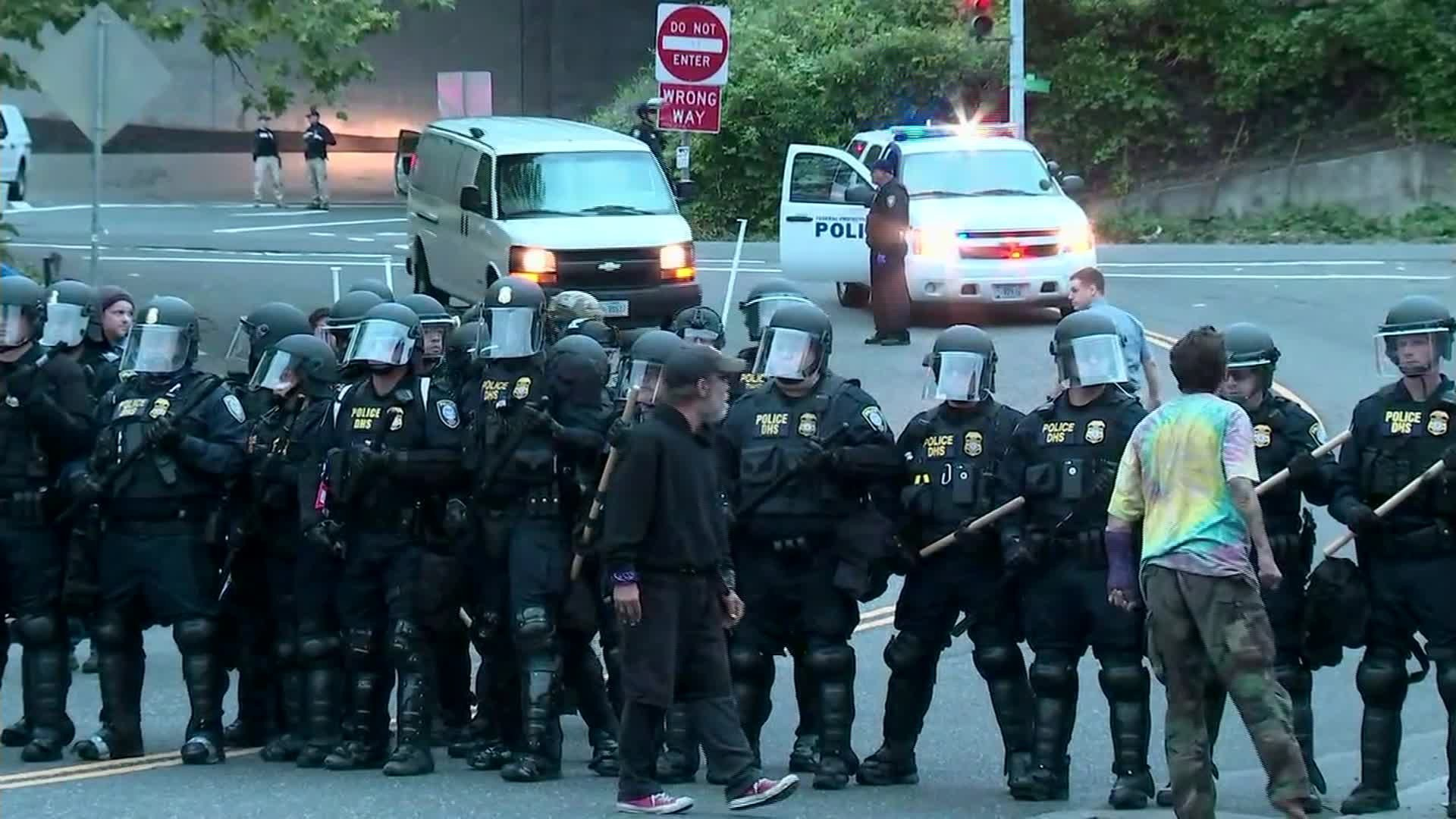 Protesters stand on June 28, 2018, near officers in riot gear as they block an entrance to the Portland ICE facility. (Credit: KPTV/CNN)