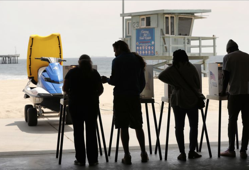From left, Gigi Grase, Jordan Loth, Glenita and husband Rick Famuyiwa, vote at the Venice Beach Lifeguard Operations Headquarters with a Venice Beach backdrop on June 5, 2018. (Credit: Al Seib / Los Angeles Times)