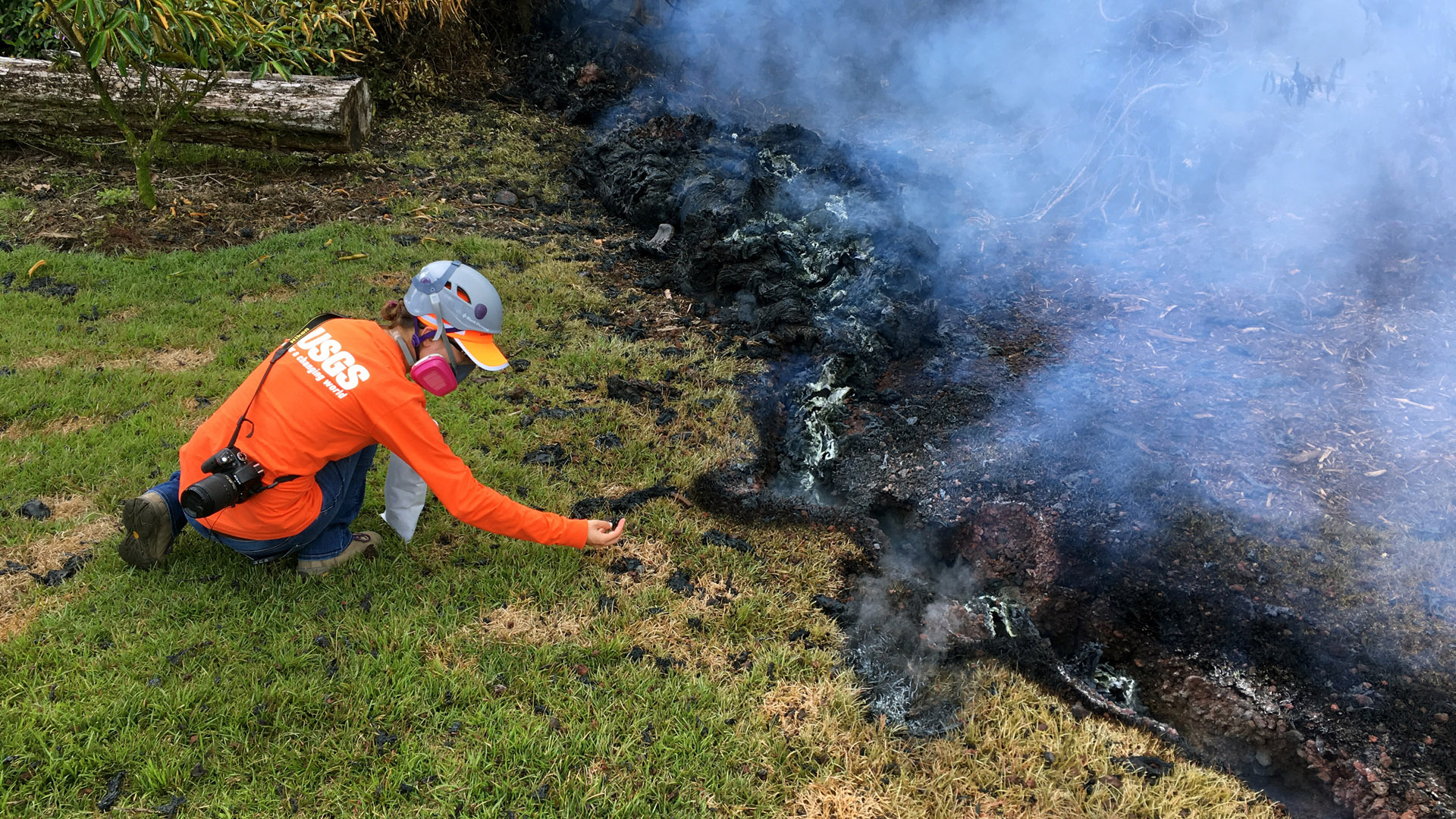 In this handout photo provided by the U.S. Geological Survey, HVO geologists collect samples of spatter for laboratory analysis after the eruption of Hawaii's Kilauea volcano on May 6, 2018 in the Leilani Estates subdivision near Pahoa, Hawaii. (Credit: U.S. Geological Survey via Getty Images)