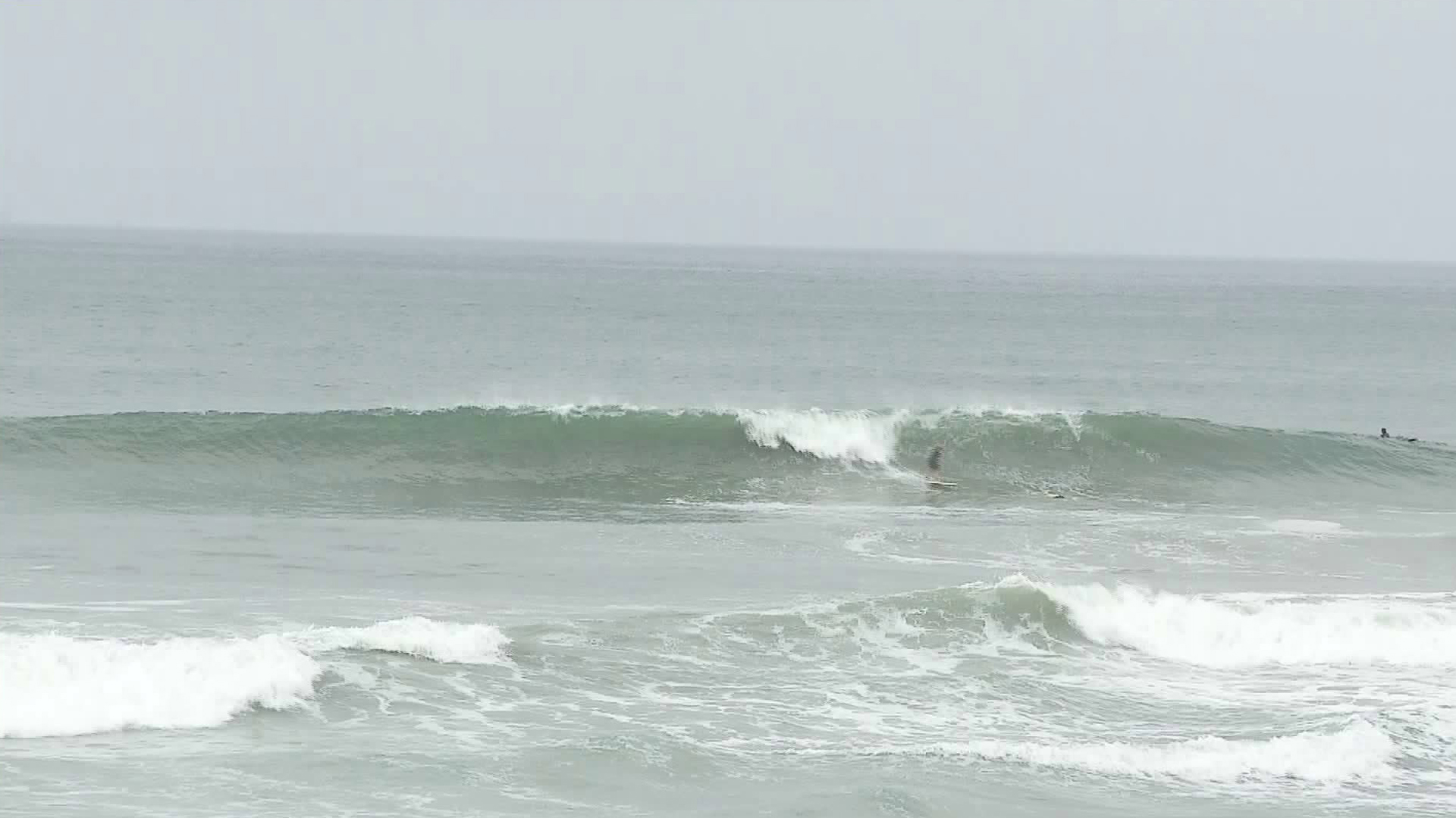 Surfers check out big waves in Huntington Beach on June 11, 2018. (Credit: KTLA)