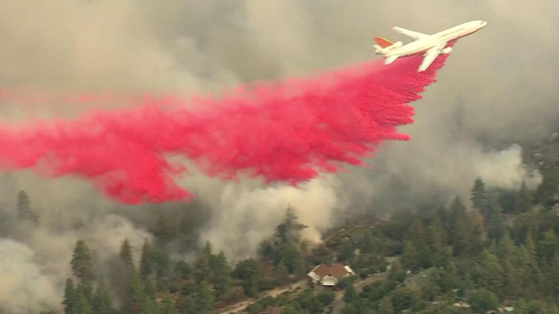 An aircraft makes a fire retardant drop as the Cranston Fire burns in Idyllwild on July 25, 2018. (Credit: KTLA)