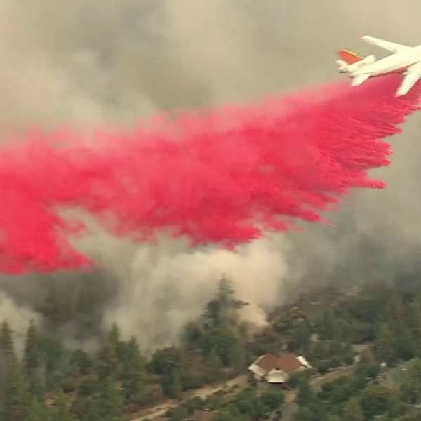 An aircraft makes a fire retardant drop as the Cranston Fire burns in Idyllwild on July 25, 2018. (Credit: KTLA)