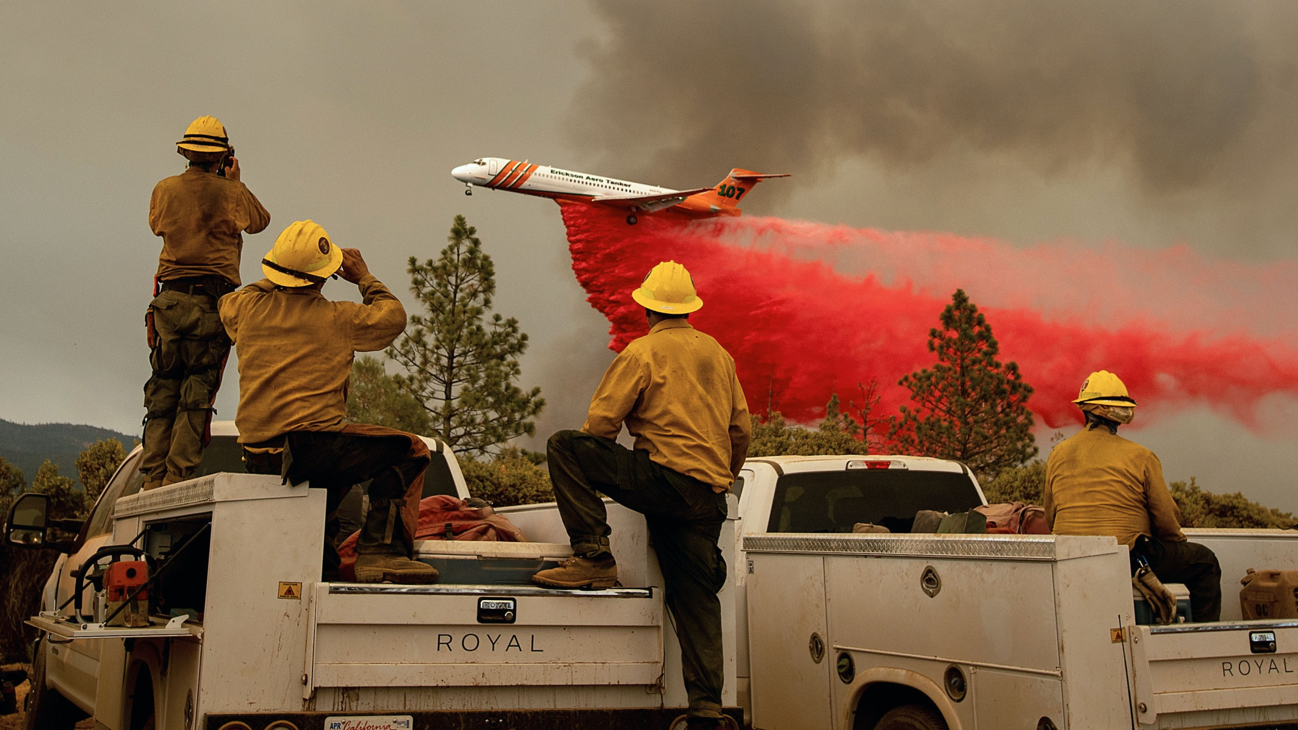 Firefighters watch as an air tanker drops retardant while battling the Ferguson fire in the Stanislaus National Forest, near Yosemite National Park, California on July 21, 2018. (Credit: NOAH BERGER/AFP/Getty Images)
