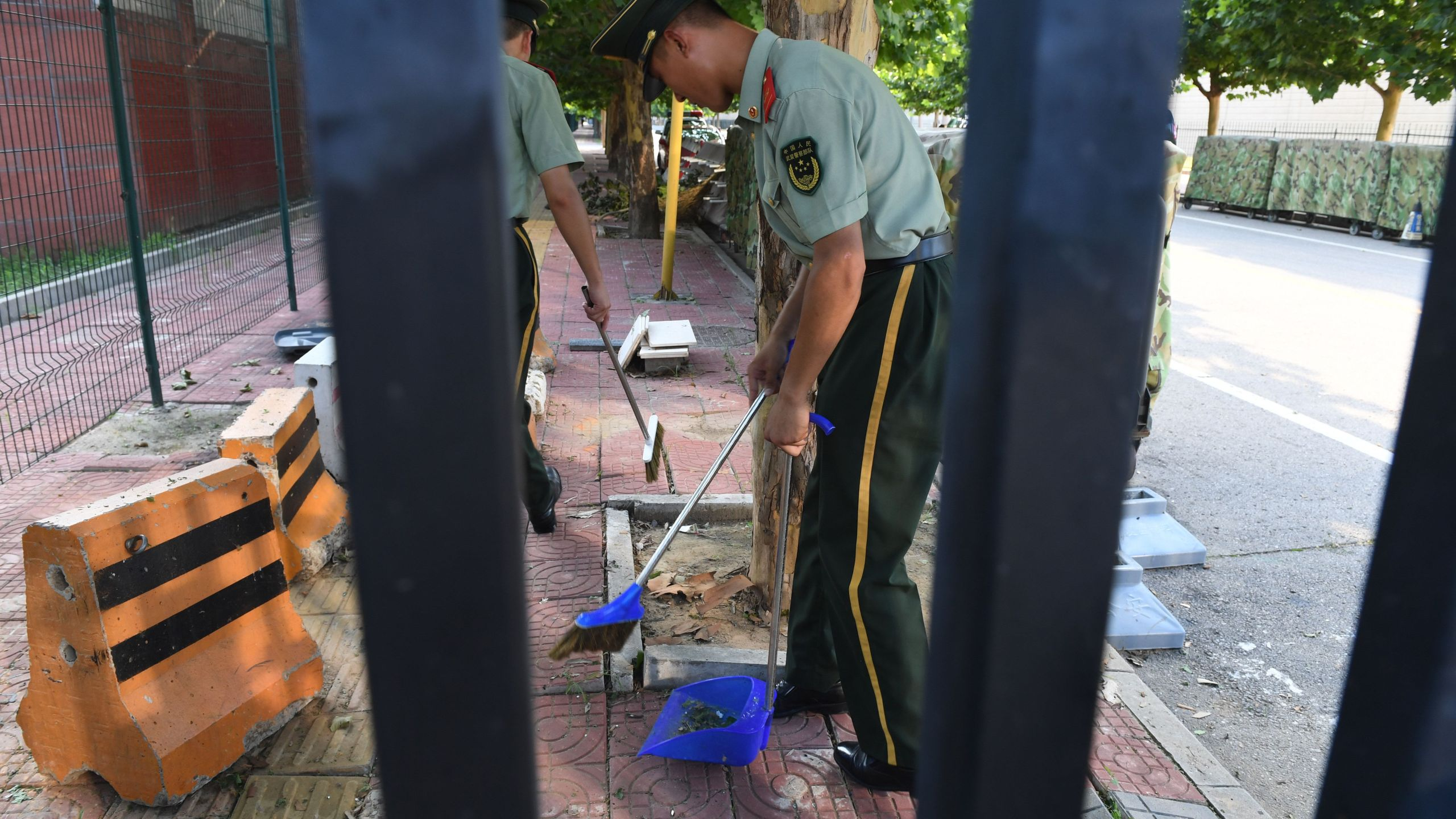 Chinese paramilitary police clean up broken glass and debris outside the US embassy compound in Beijing on July 26, 2018 following a blast near the embassy premises. (Credit: GREG BAKER/AFP/Getty Images)