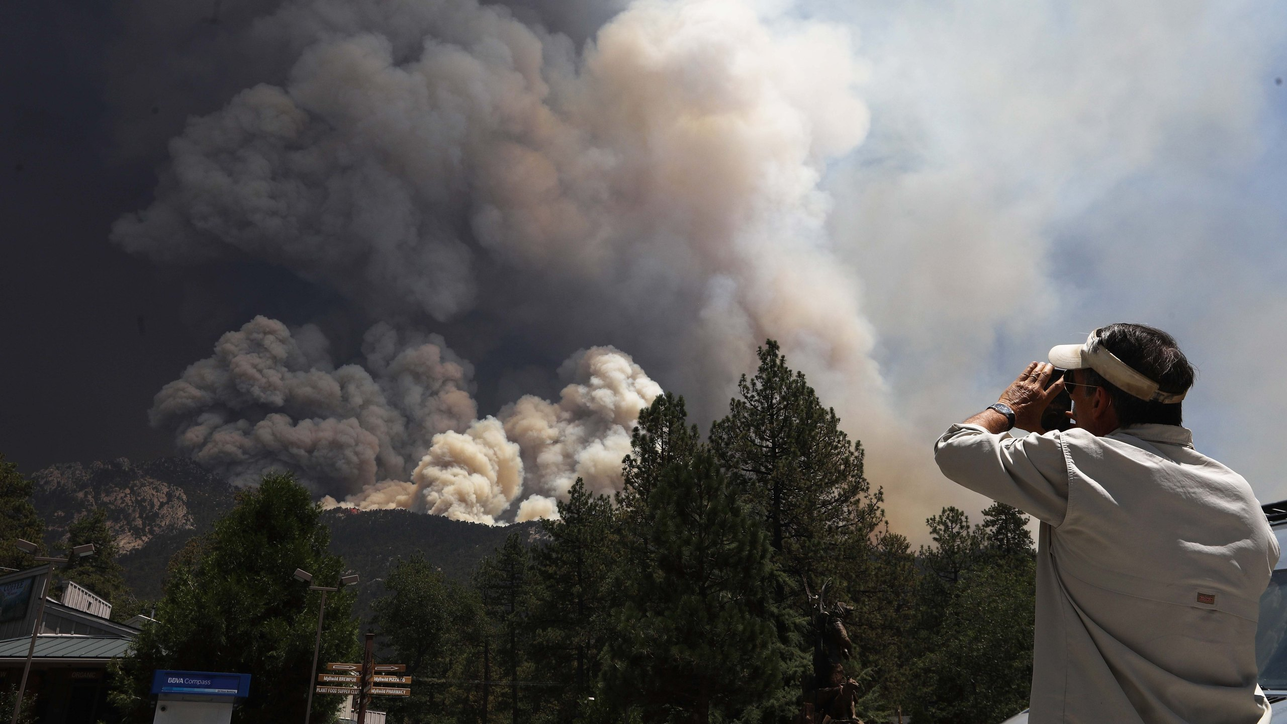 The Cranston Fire burns as a man takes photos near Idyllwild on July 26, 2018. (Credit: Mario Tama / Getty Images)