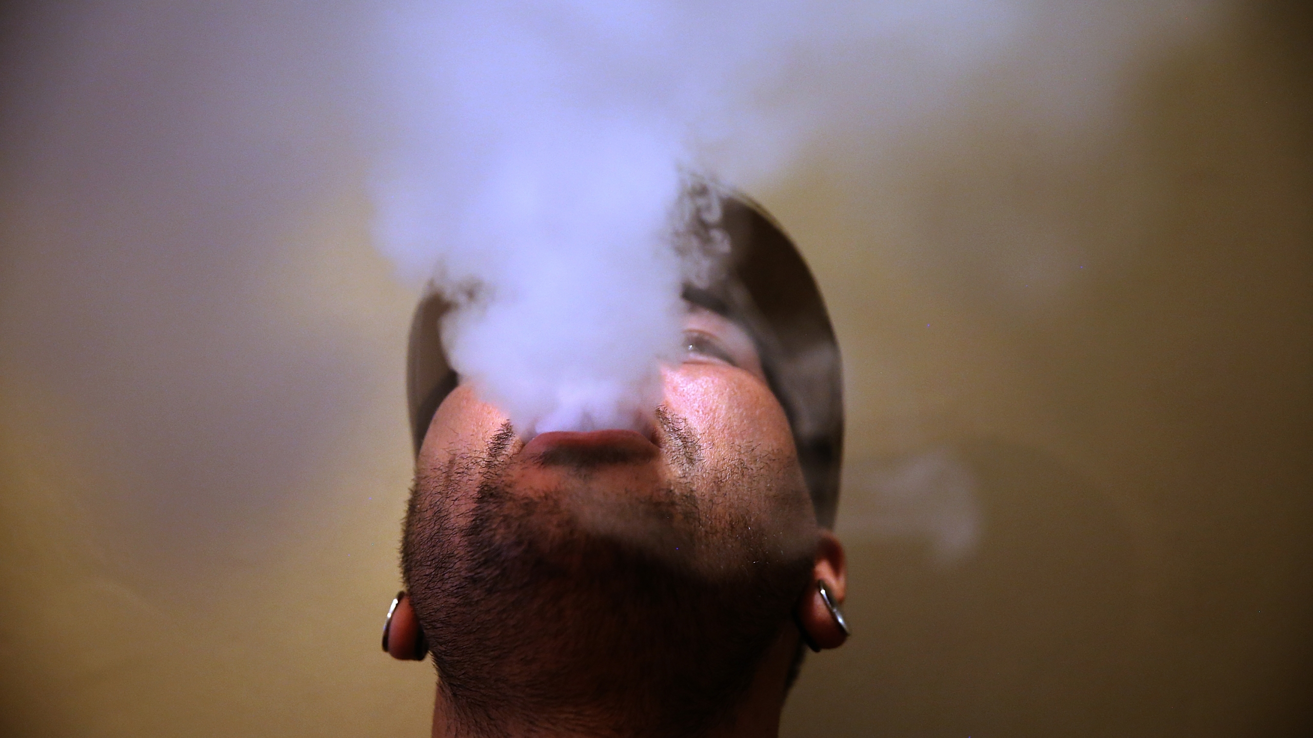 A person blows vapor from an e-cigarette on May 5, 2016 in San Francisco. (Credit: Justin Sullivan/Getty Images)