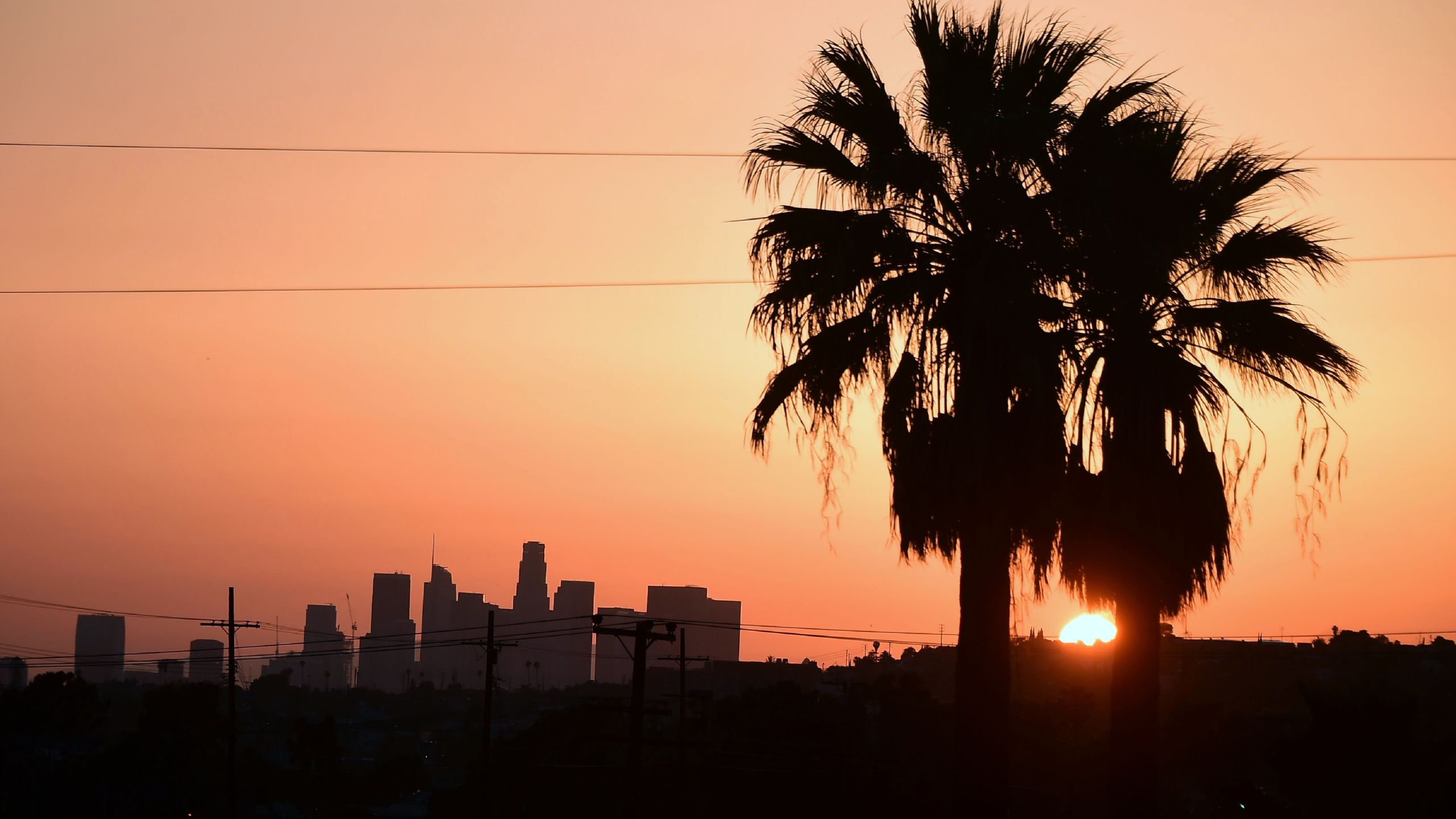 The sun sets behind the downtown Los Angeles skyline on April 11, 2017. (Credit: FREDERIC J. BROWN/AFP/Getty Images)