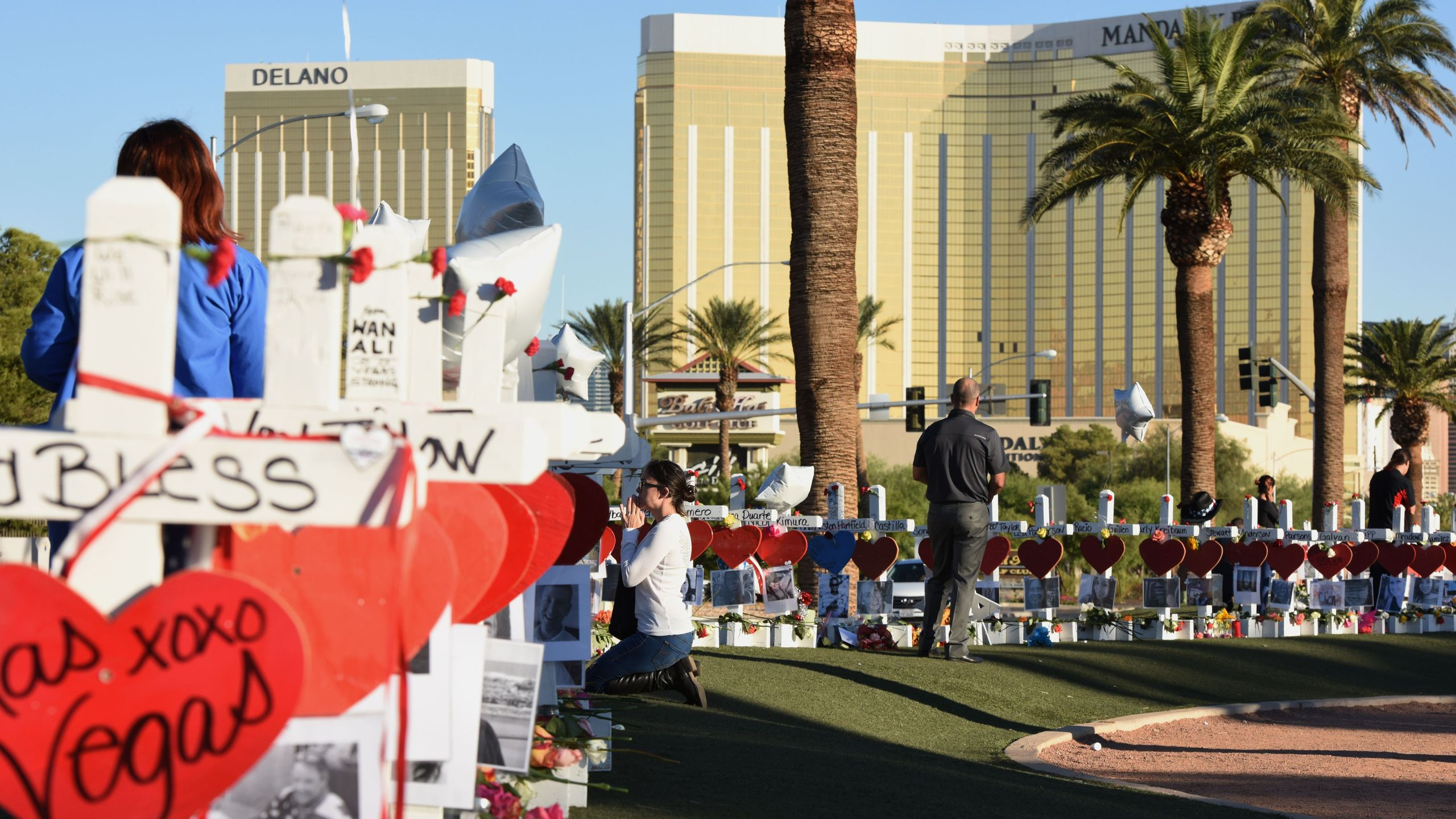 A woman prays beside 58 white crosses for the victims of a mass shooting on the Las Vegas Strip just south of the Mandalay Bay hotel on Oct. 6, 2017. (Credit: ROBYN BECK/AFP/Getty Images)