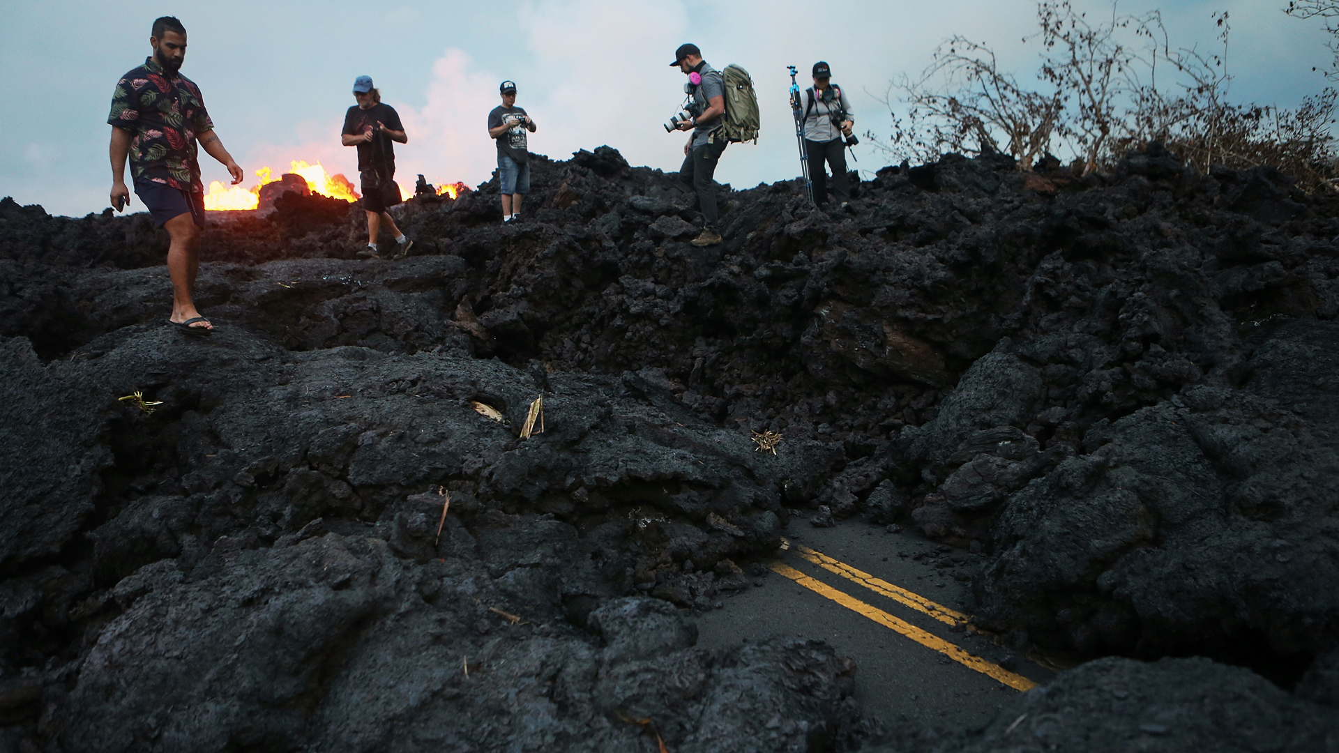 Onlookers and photographers walk on hardened lava from a Kilauea volcano fissure as lava erupts in Leilani Estates, on Hawaii's Big Island, on May 26, 2018. (Credit: Mario Tama/Getty Images)