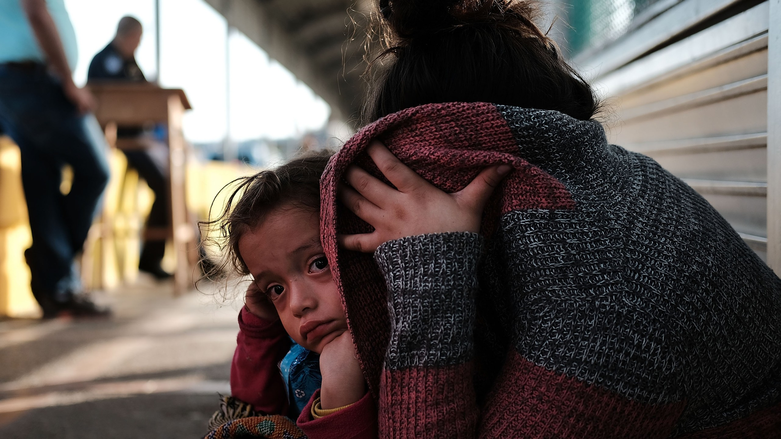 A Honduran child and her mother, fleeing poverty and violence in their home country, waits along the border bridge after being denied entry from Mexico into the U.S. on June 25, 2018 in Brownsville, Texas. (Credit: Spencer Platt/Getty Images)