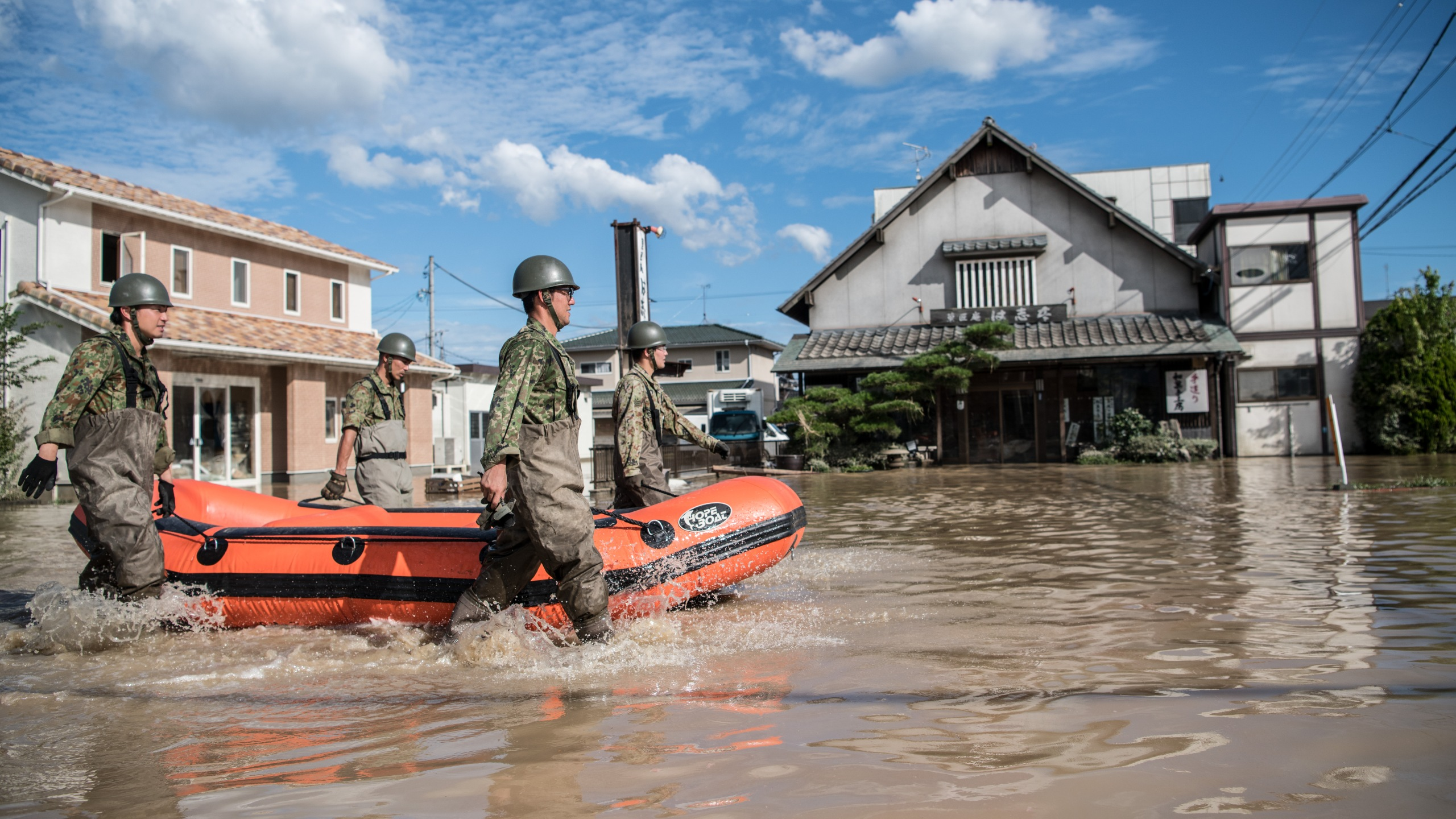 Soldiers push a boat as they prepare to search for survivors following heavy flooding, on July 8, 2018 in Kurashiki near Okayama, Japan. (Credit: Carl Court/Getty Images)