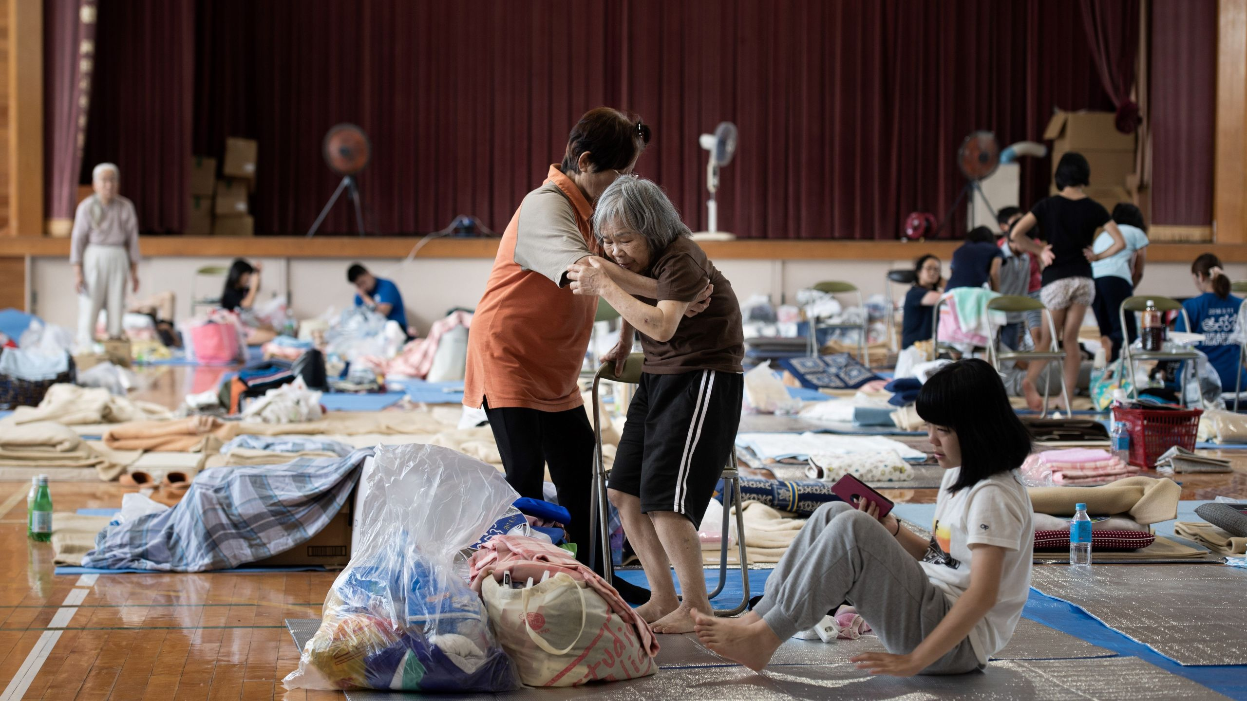 A woman is given assistance as people affected by the recent flooding in Japan rest at a makeshift shelter in Mabi, Okayama on July 11, 2018. (Credit: Martin Bureau/AFP/Getty Images)
