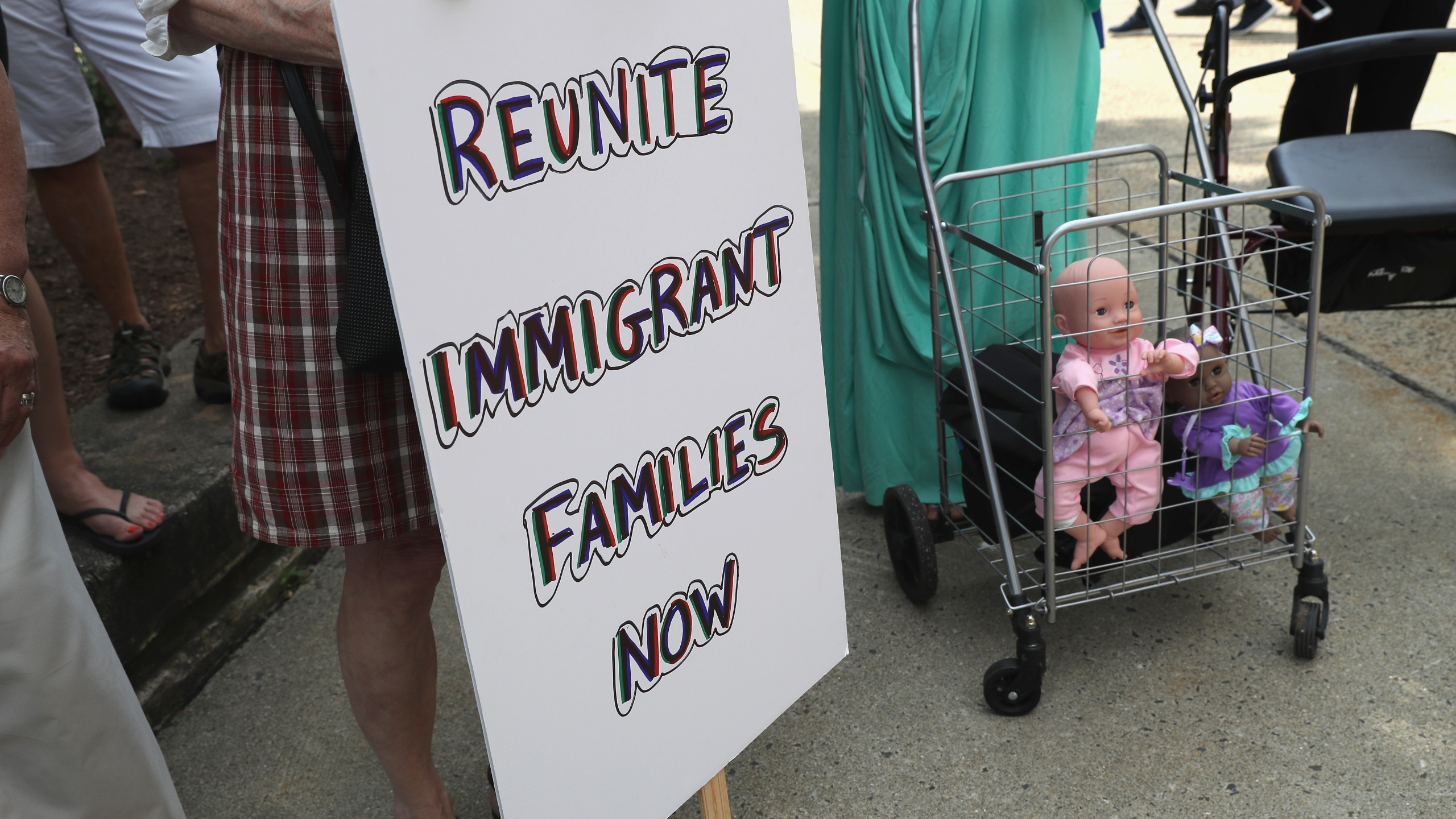 Dolls stand in a shopping cart as protesters rally against the separation of immigrant families in front of a U.S. federal court on July 11, 2018 in Bridgeport, Connecticut. (Credit: John Moore/Getty Images)