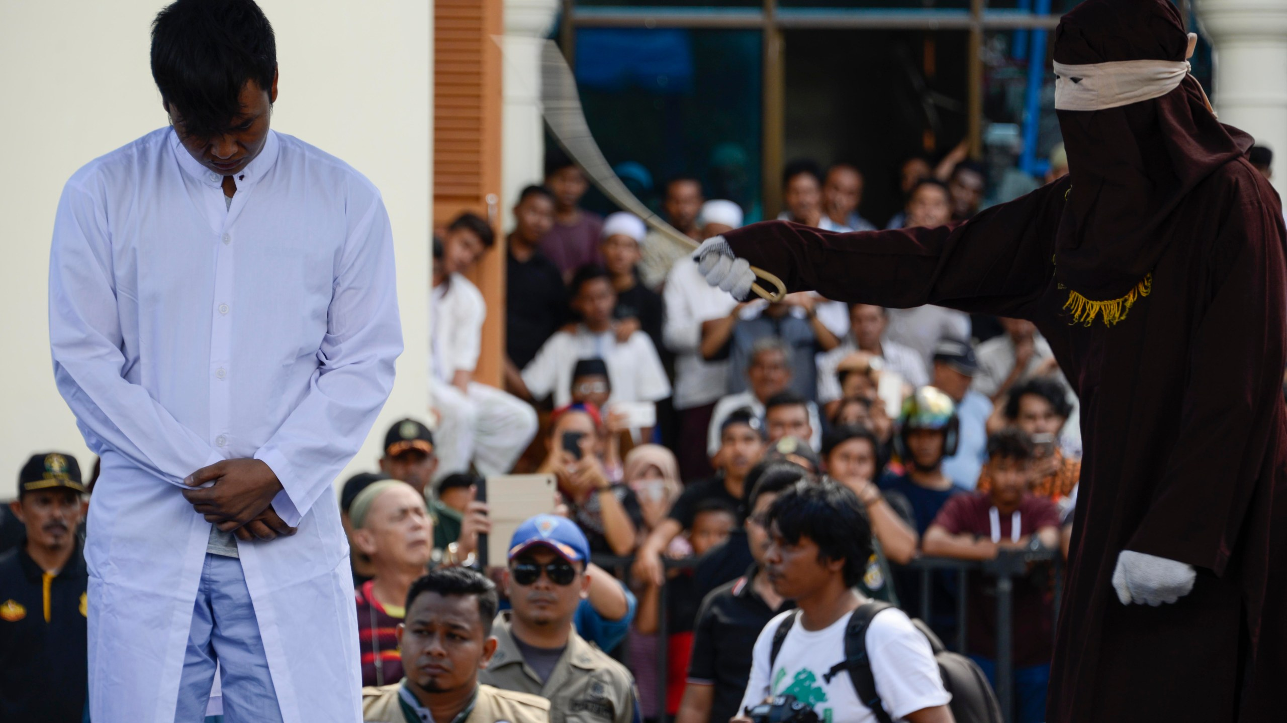 A member of Indonesia's Sharia police, right, whips a man, left, accused of having gay sex during a public caning ceremony outside a mosque in Banda Aceh, capital of Aceh province on July 13, 2018. (Credit: Chaideer Mahyuddin/AFP/Getty Images)
