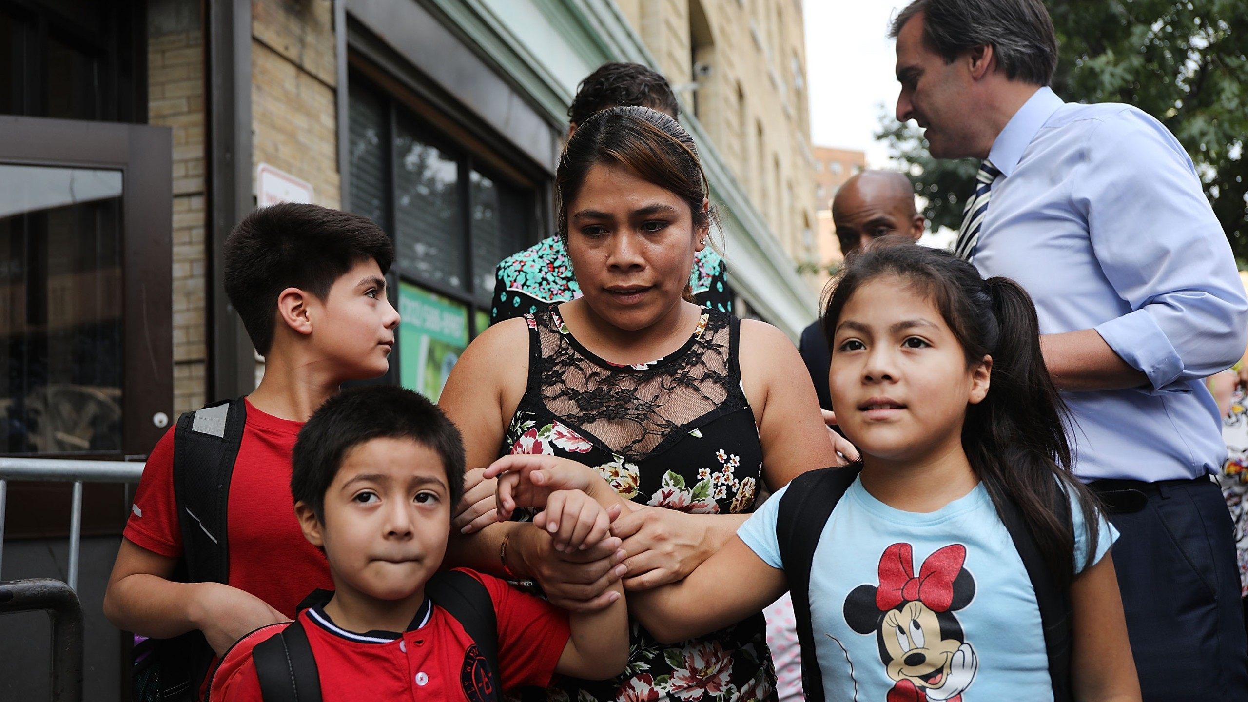 Yeni Maricela Gonzalez Garcia (center) stands with her children, 6-year-old Deyuin (left), 9-year-old Jamelin (right) and 11-year-old Lester (back) as she and her lawyer speak with the news media after the family was reunited at the East Harlem Cayuga Centers in New York City on July 13, 2018. (Credit: Spencer Platt / Getty Images)