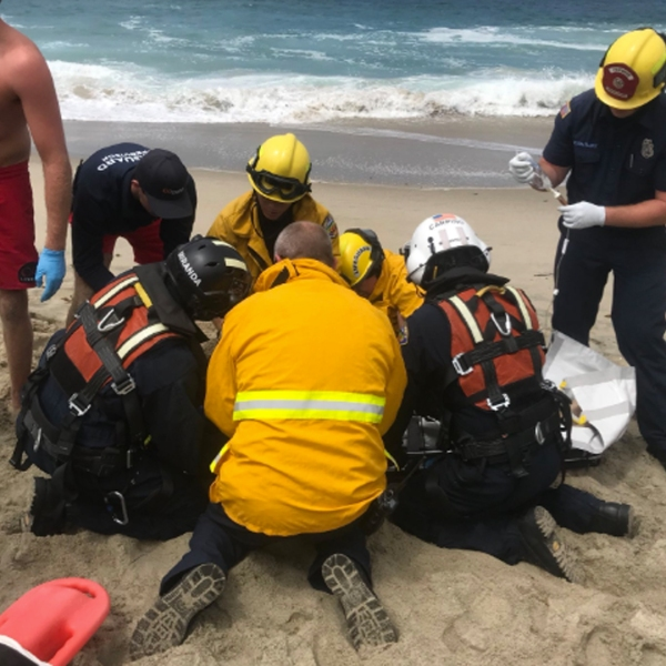 Authorities are shown trying to help a swimmer on July 14, 2018 at 1000 Steps Beach in Laguna Beach. (Credit: Laguna Beach Police Department Public Information Officer Sgt. Jim Cota's Twitter Account).