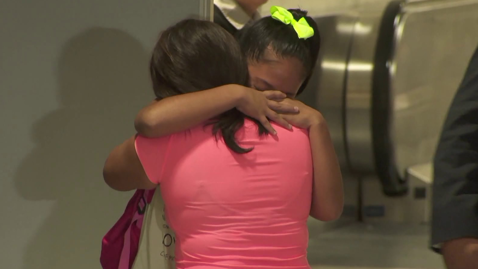Perla De Velasquez hugs her 12-year-old daughter, Yoselin, tightly as the two are reunited at LAX on July 1, 2018, after more than a month apart. They had been separated by federal immigration authorities. (Credit KTLA)