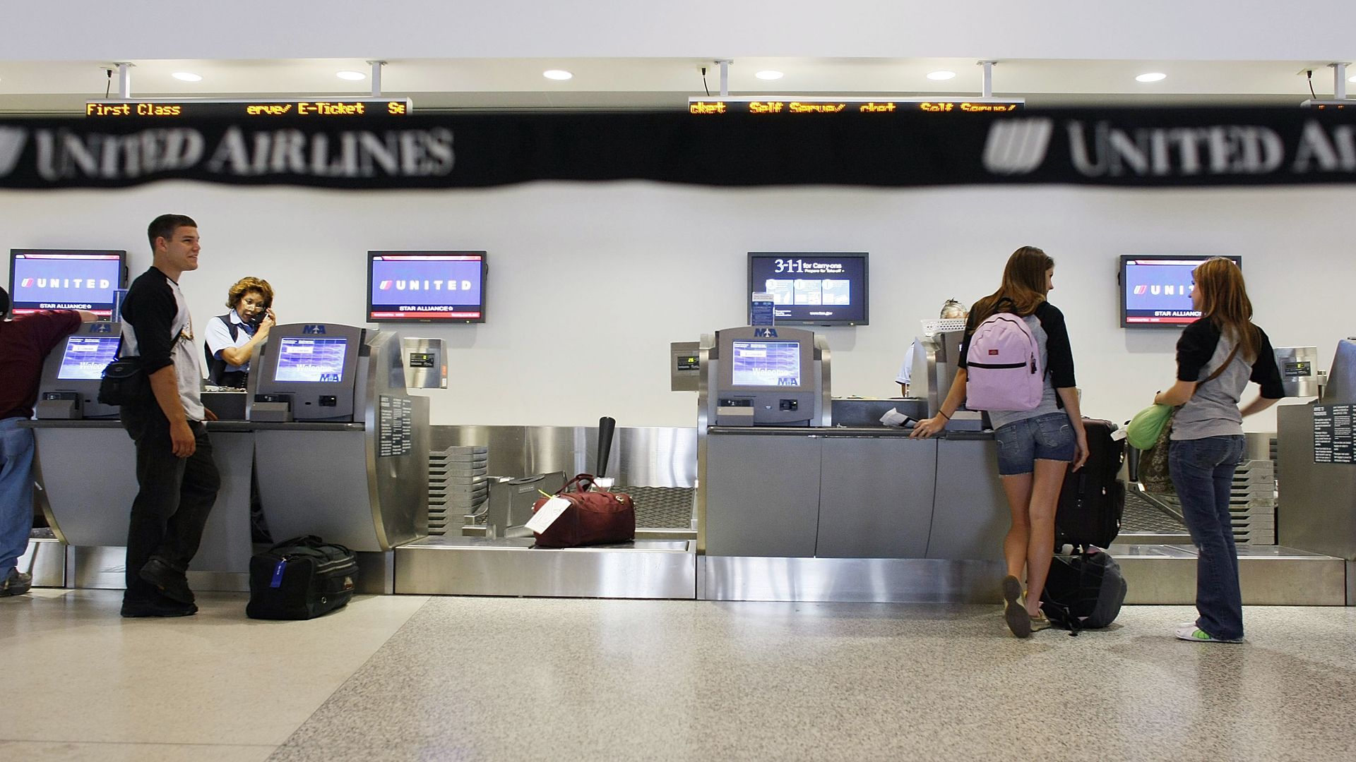 In this file photo, passengers check in with their baggage at the United Airlines counter at the Miami International Airport in Miami. (Credit: Joe Raedle/Getty Images)
