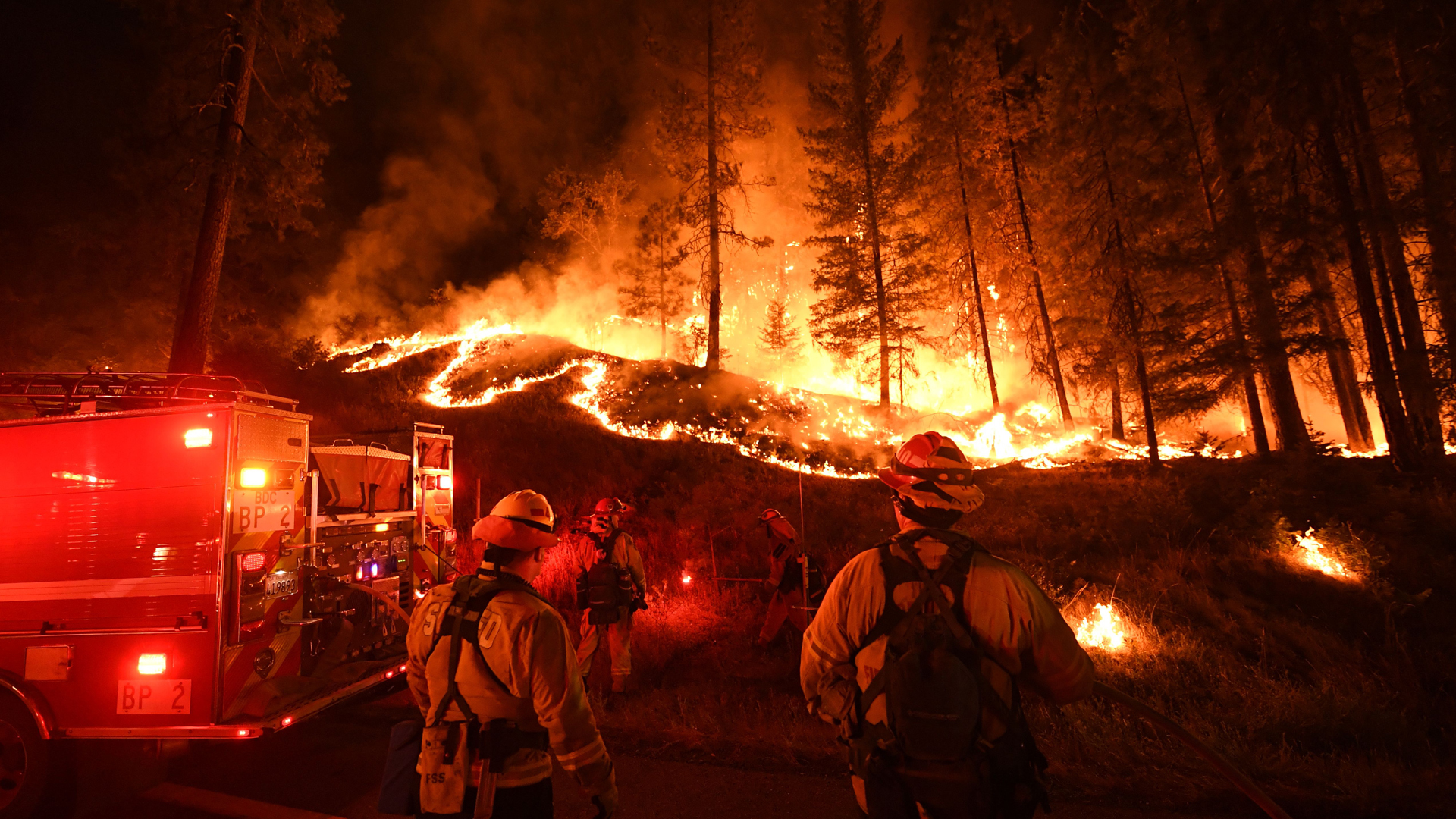 Firefighters try to control a back burn as the Carr Fire spreads toward the towns of Douglas City and Lewiston near Redding on July 31, 2018. (Credit: MARK RALSTON/AFP/Getty Images)