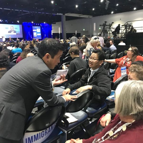 In this undated photo, Dave Min, left, lobbies California Democratic Party delegates on the convention floor, asking them to support his endorsement ahead of the primaries in 2018. (Credit: Javier Panzar / Los Angeles Times)