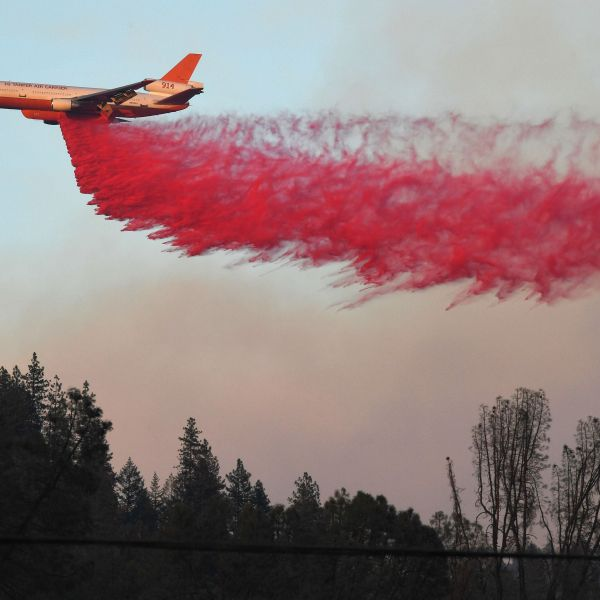 An air tanker drops fire retardant to try to contain flames from the Carr Fire as it spreads towards the town of Lewiston near Redding on Aug. 2, 2018. (Credit: MARK RALSTON/AFP/Getty Images)