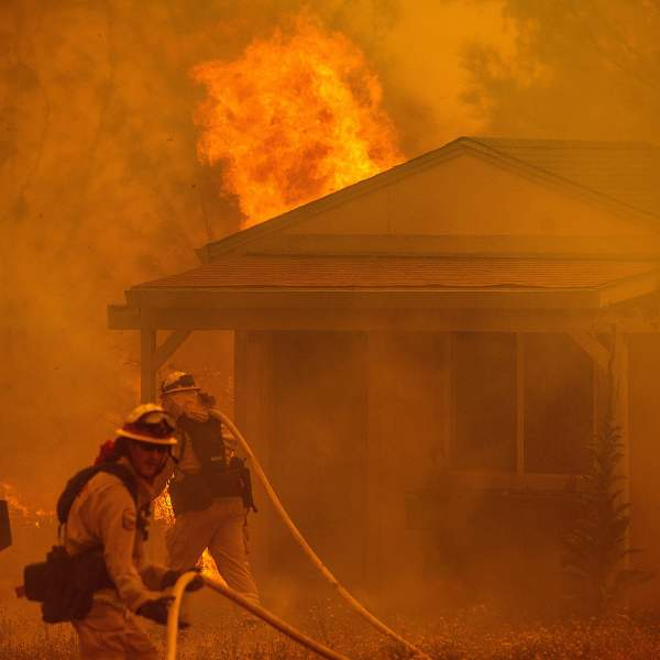 Firefighters fight to save a structure on New Long Valley Rd as the Ranch Fire burns near Clearlake Oaks, California on Aug. 4, 2018. (Credit: NOAH BERGER/AFP/Getty Images)
