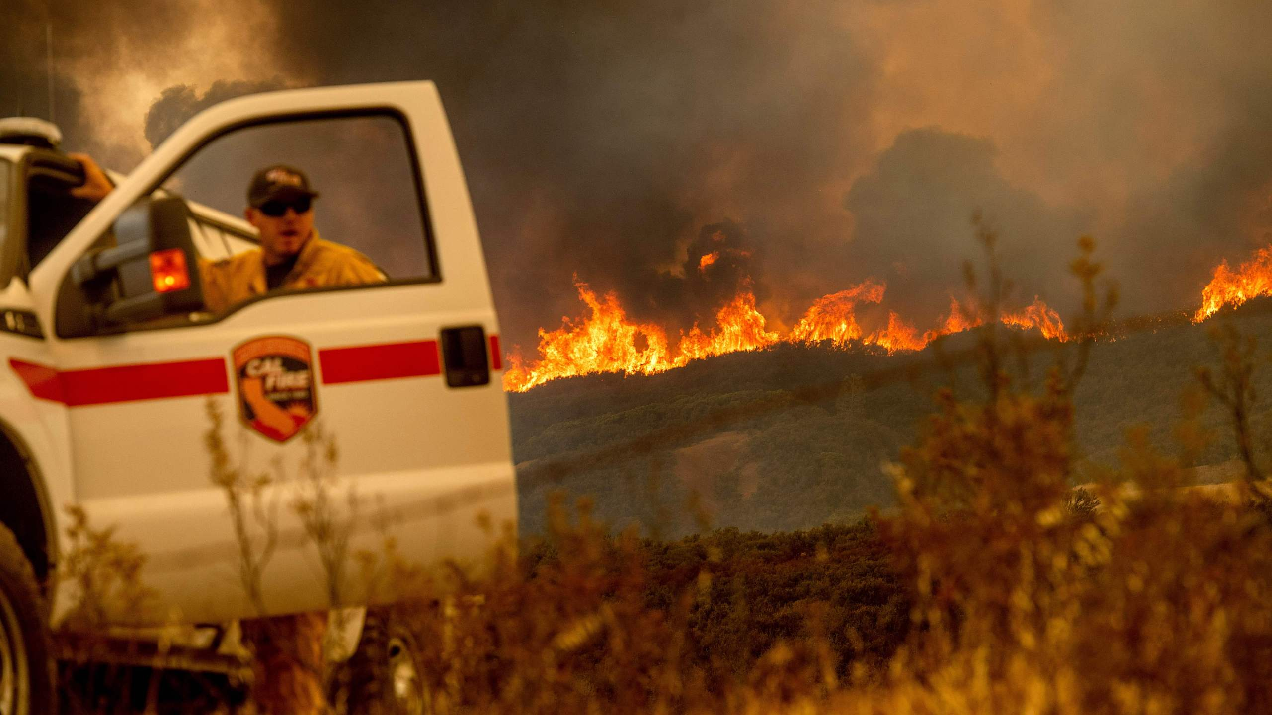 The Ranch Fire, part of the Mendocino Complex Fire, crests a ridge as Cal Fire Battalion Chief Matt Sully directs firefighting operations near Clearlake Oaks on Aug. 5, 2018. (Credit: Noah Berger / AFP / Getty Images)