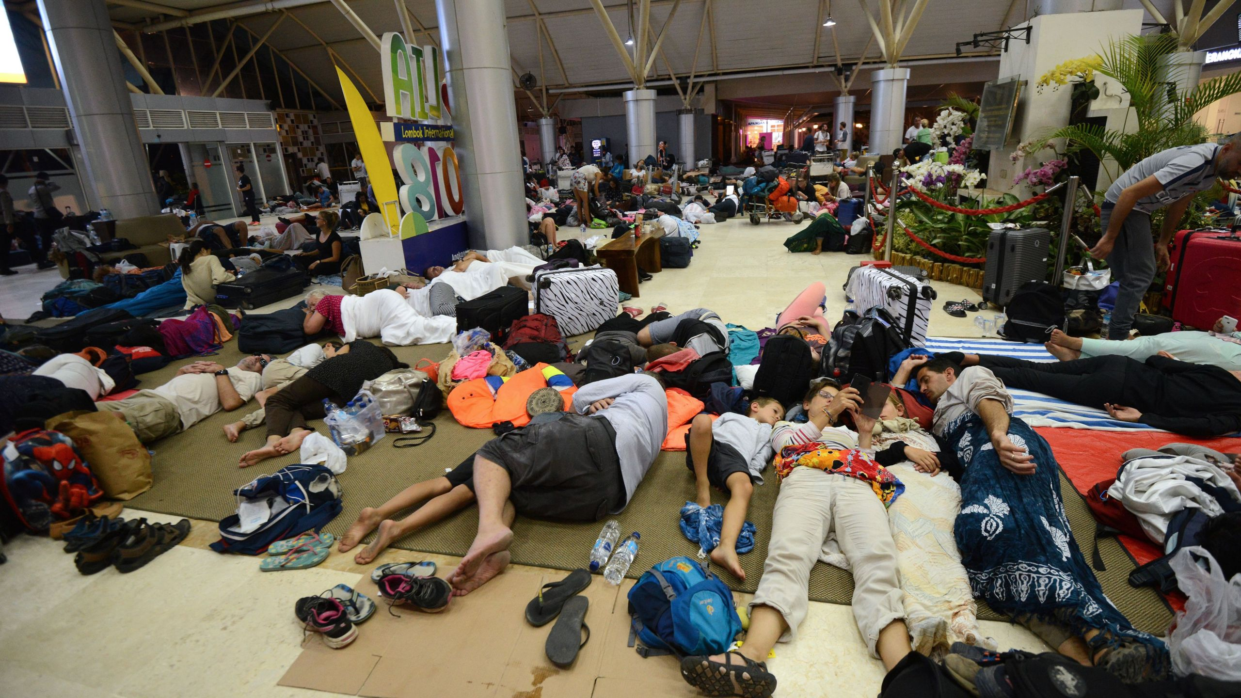 Tourists sleep while waiting to depart from the Praya Lombok International Airport on the West Nusa Tenggara province on Aug. 6, 2018. (Credit: SONNY TUMBELAKA/AFP/Getty Images)