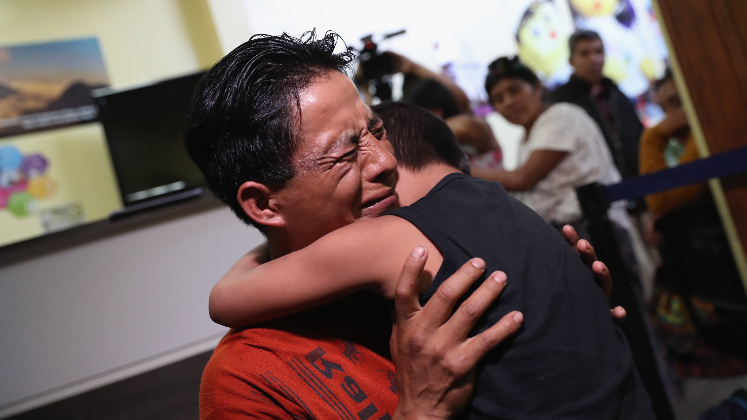 "A father embraces his son for the first time in months on Aug. 7, 2018 in Guatemala City, Guatemala. A group of nine children were flown from New York and reunited with their families, months after U.S. border agents separated them and deported the parents as part of the Trump administration's ""zero tolerance"" policy at the border. (Credit: John Moore/Getty Images)"